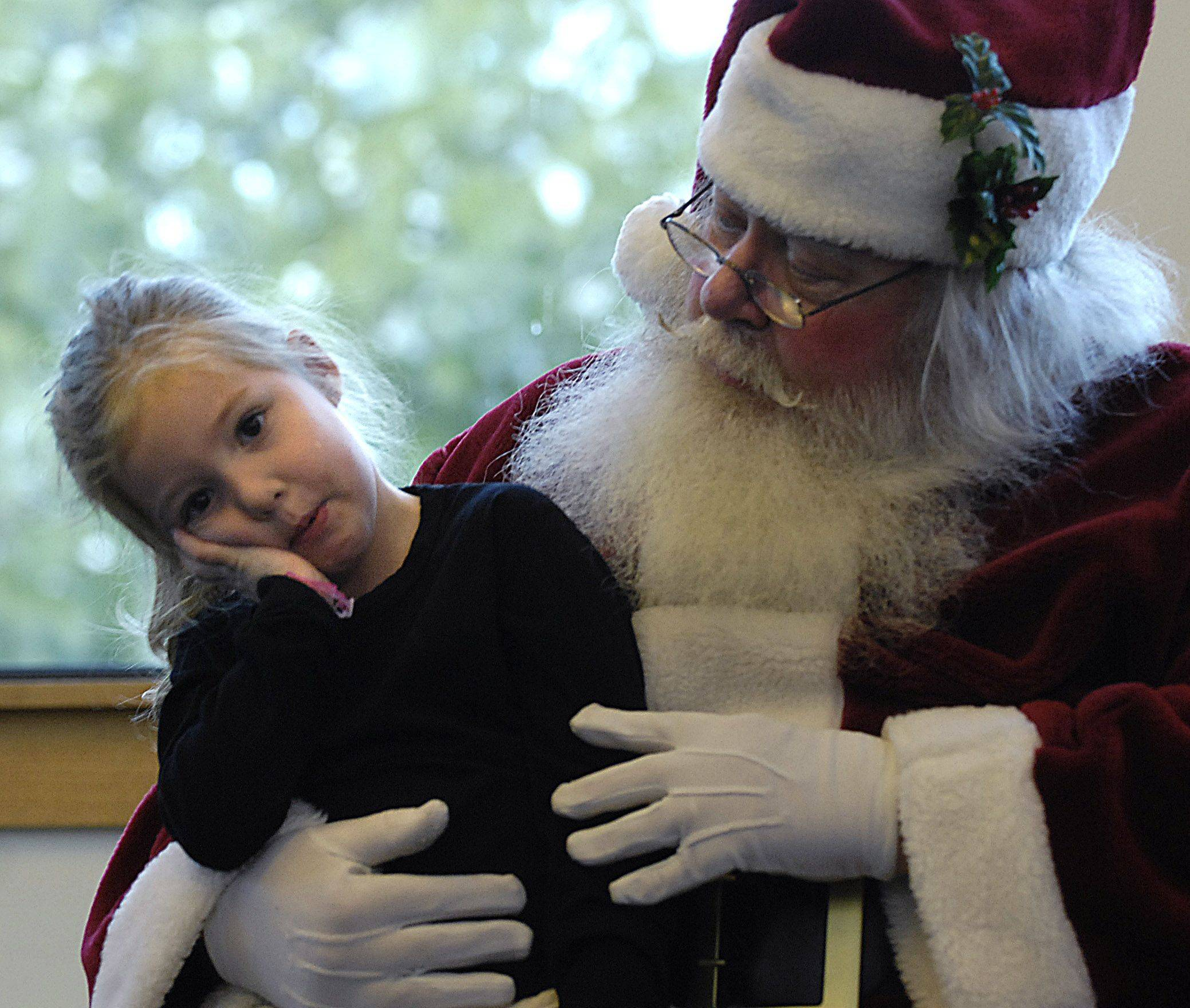 Vera Indelli thinks about her answer as she speaks with Santa Claus at the Messenger Public Library's annual Holiday Open House Sunday in North Aurora Sunday. She was with her dad Bill of North Aurora. A balloon artist, a face-painter and other activities rounded out the day.