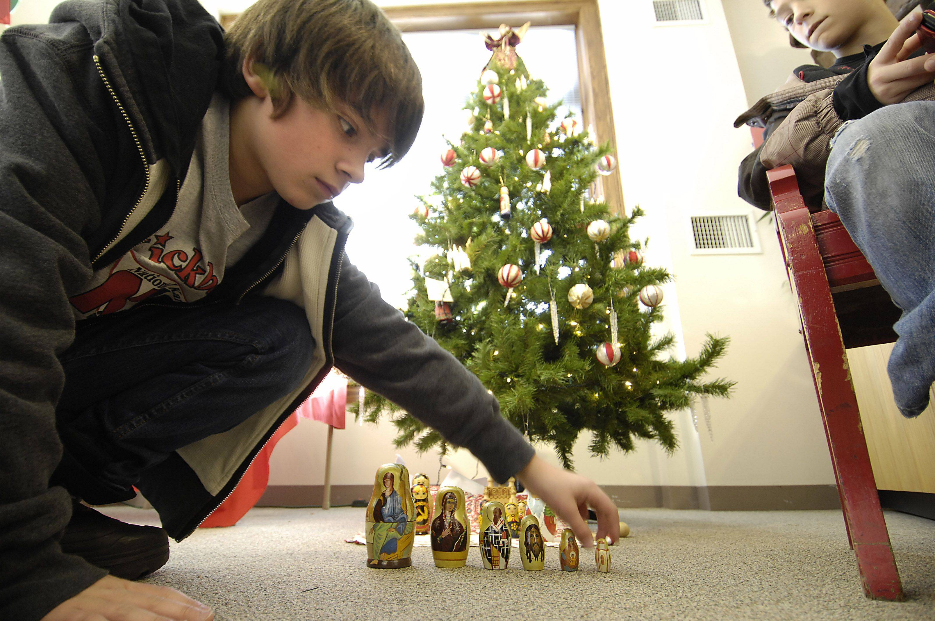 Henry Myers, 14, inspects Russian Christmas babushka nesting doll decorations Sunday at the Elgin Public Museum's Touching on Traditions exhibit. The exhibit features more than 50 displays of holiday significance from countries around the globe. Henry was with his dad Art and brother Andy. He was at the museum to gather information for a school project. The holiday exhibit will be shown every day starting Dec. 18 until the end of the month.