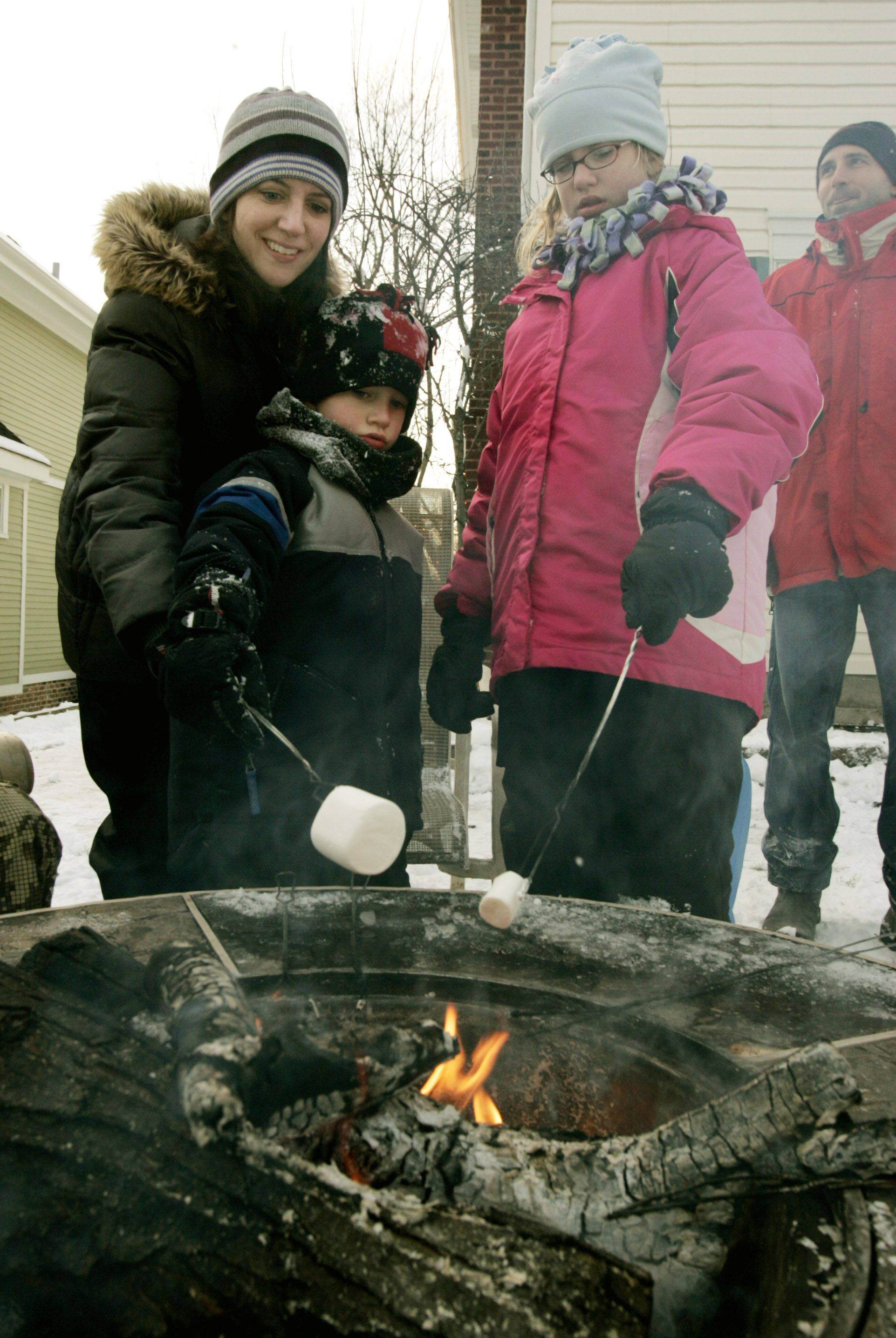 Anita Devalk of Itasca and her children Evan, 6, and Emma, 10, work on marshmallows during the Itasca Block Party Sunday along Maple Street in Itasca.