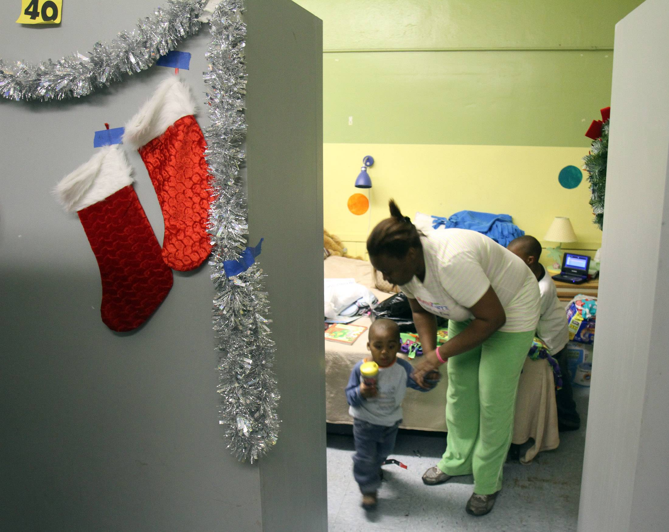 Latoya Hawkins gets ready for dinner with her 1 year old son Jermain at the pads family center in Waukegan Monday. Her living area was decorated with garland and Christmas stcokings. The facility is a 24 hour home for 42 clients.