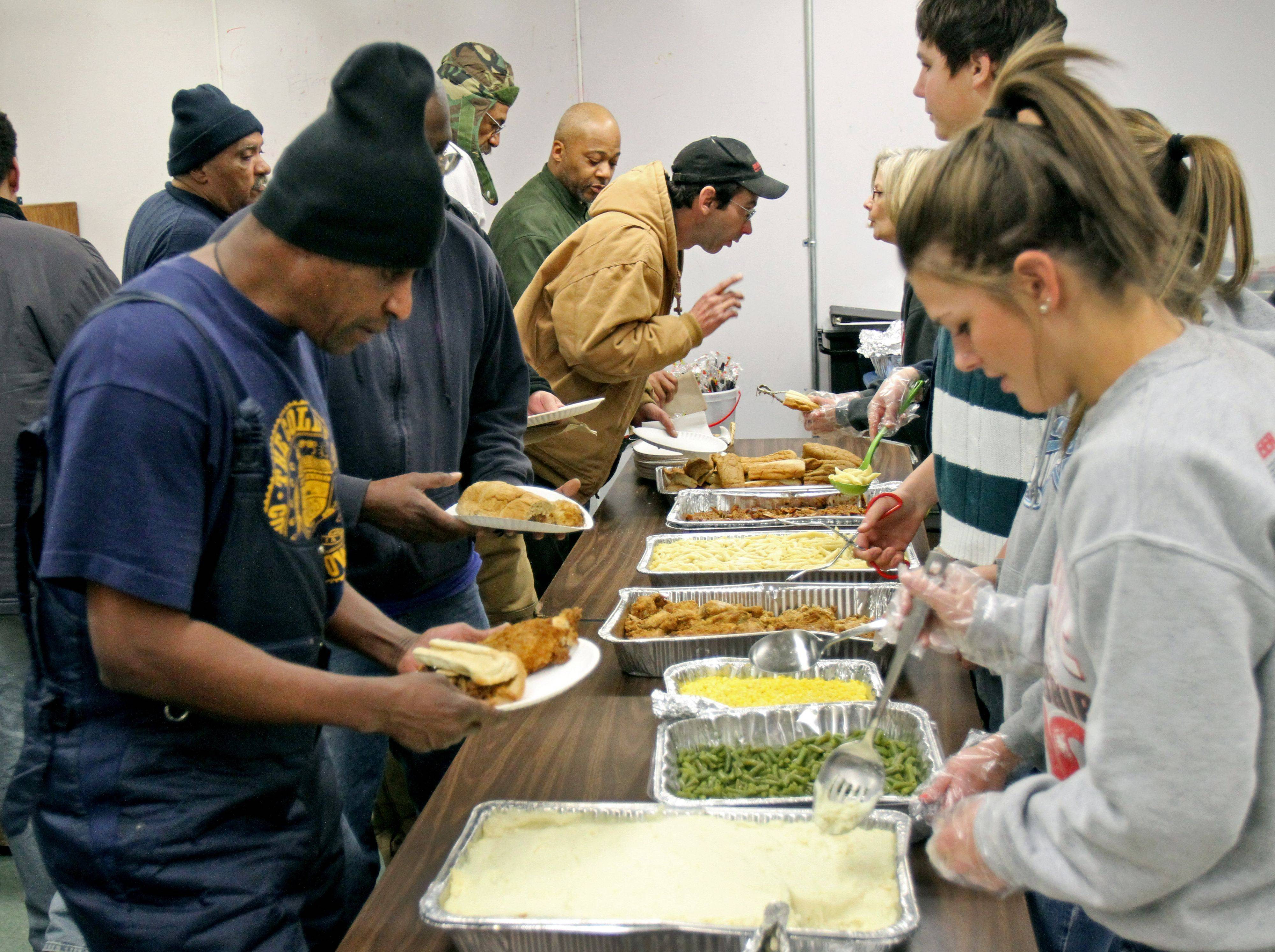 PADS guests line up for a meal as volunteers dish out some food at the Libertyville PADS shelter sponsored by St. Joseph Catholic Church Wednesday. Many of the volunteers were from First Presbyterian Church in Libertyville. About 35 men showed up to the facility Wednesday.