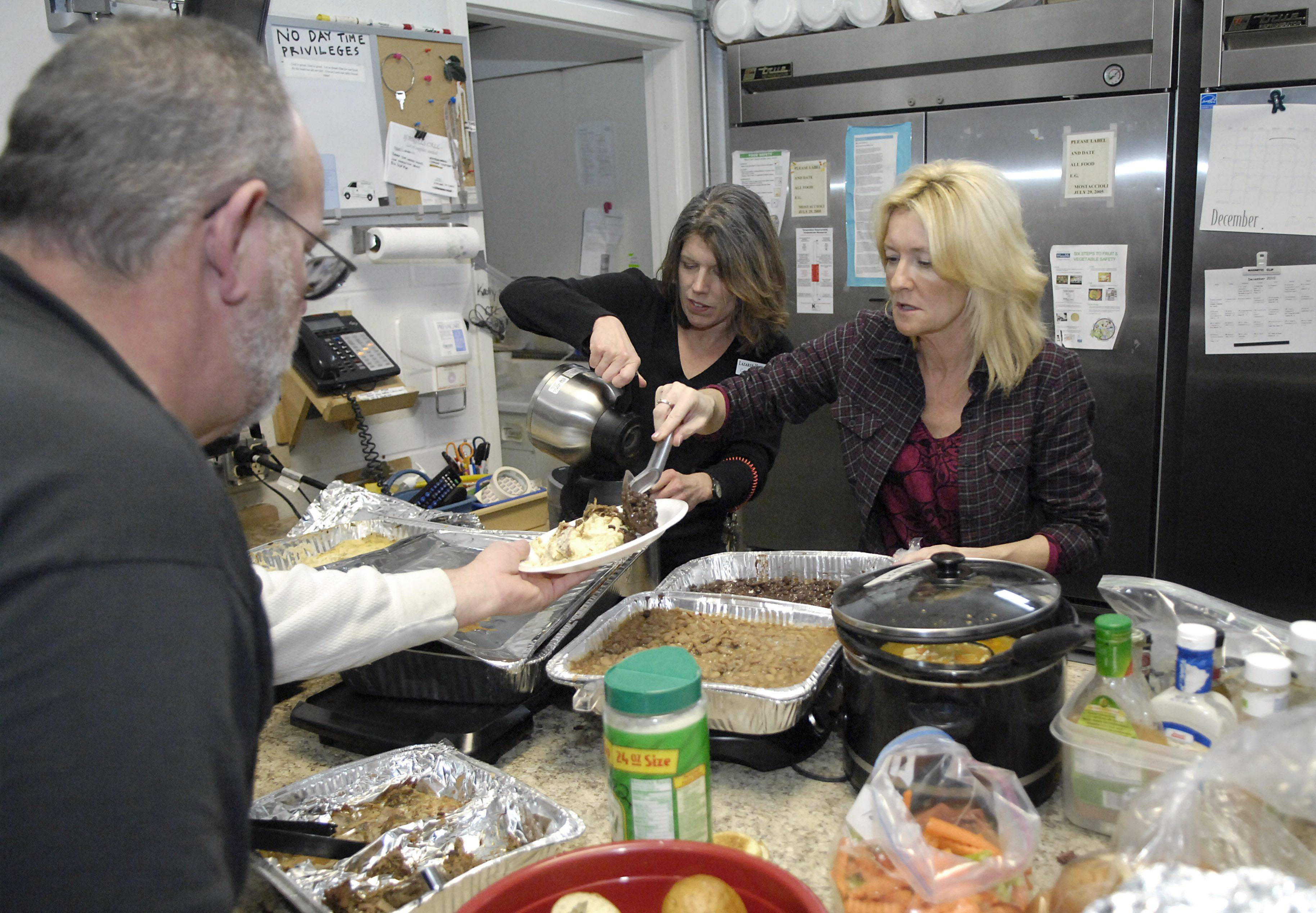 Lazarus House Operations Manager Carol Migacz, left, and volunteer Lisa Drummond help serve lunch at the homeless shelter in St. Chalres on Thursday, December 9. At least a dozen people were on hand for the start of lunch and a few more filtered in as the lunch hour went on.