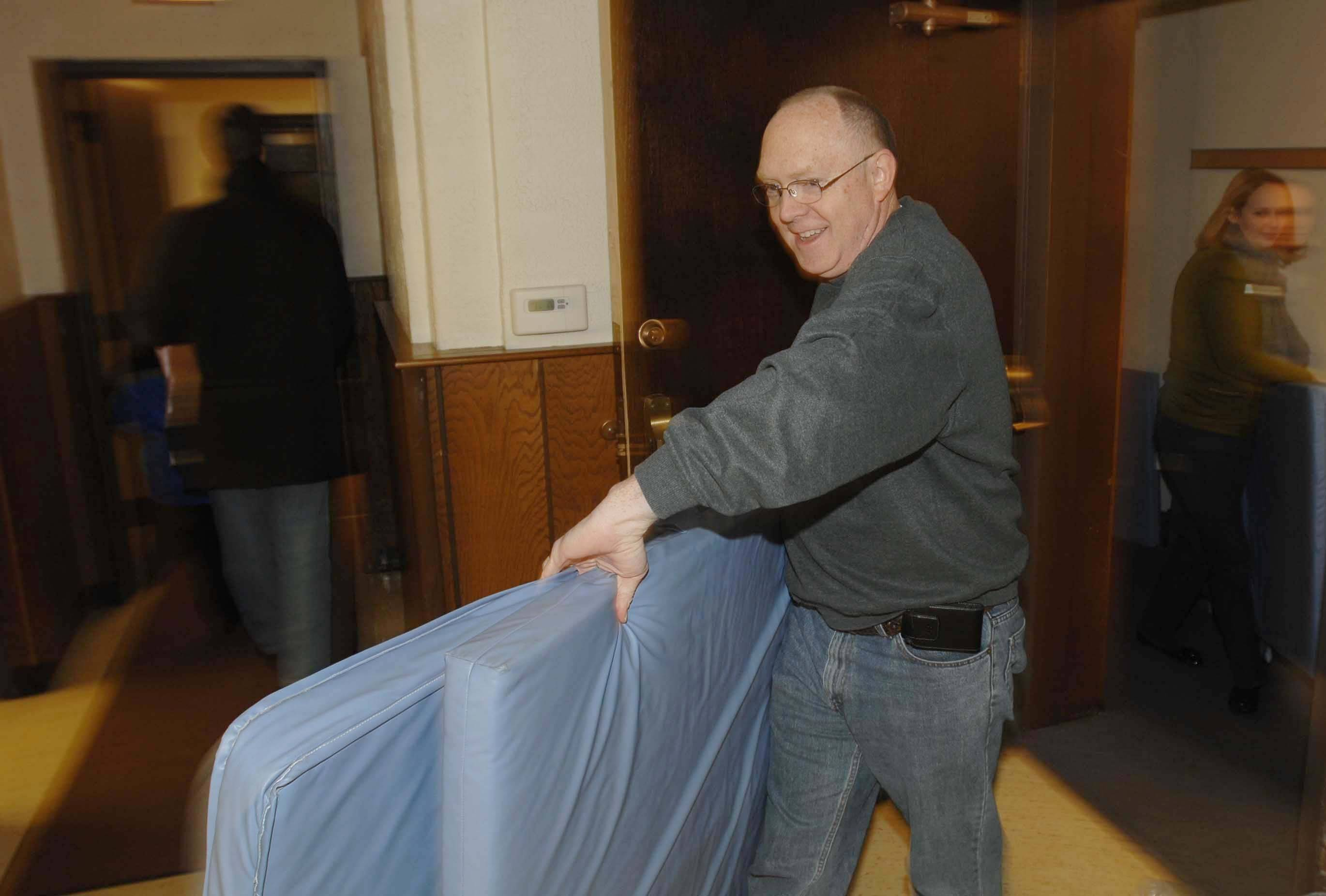 Mark Lindley of Naperville pulls pads into the PADS shelter at First Congregational Church in Naperville Wednesday.