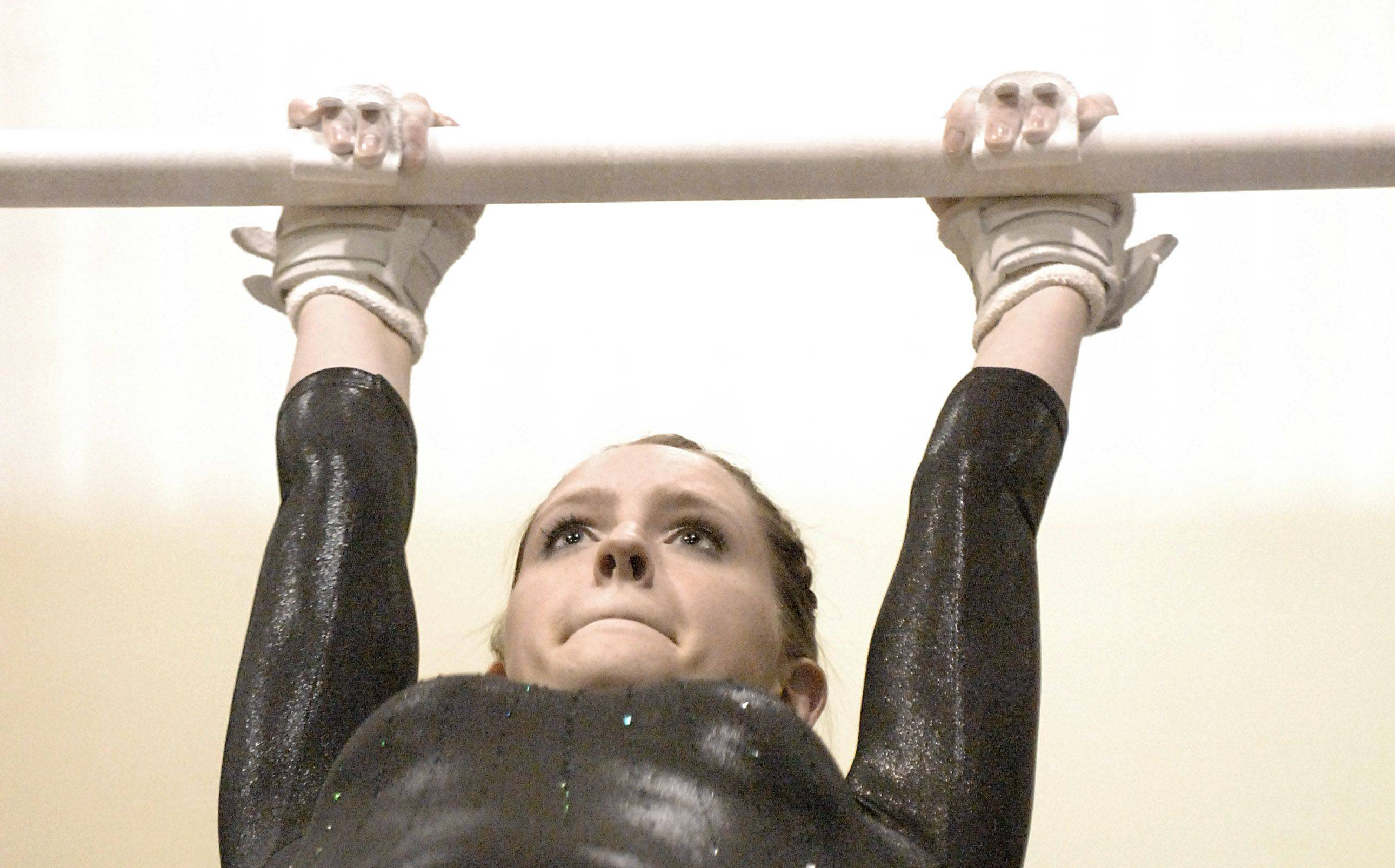 Waubonsie Valley's Torie Winslow competes on the uneven bars Wednesday.