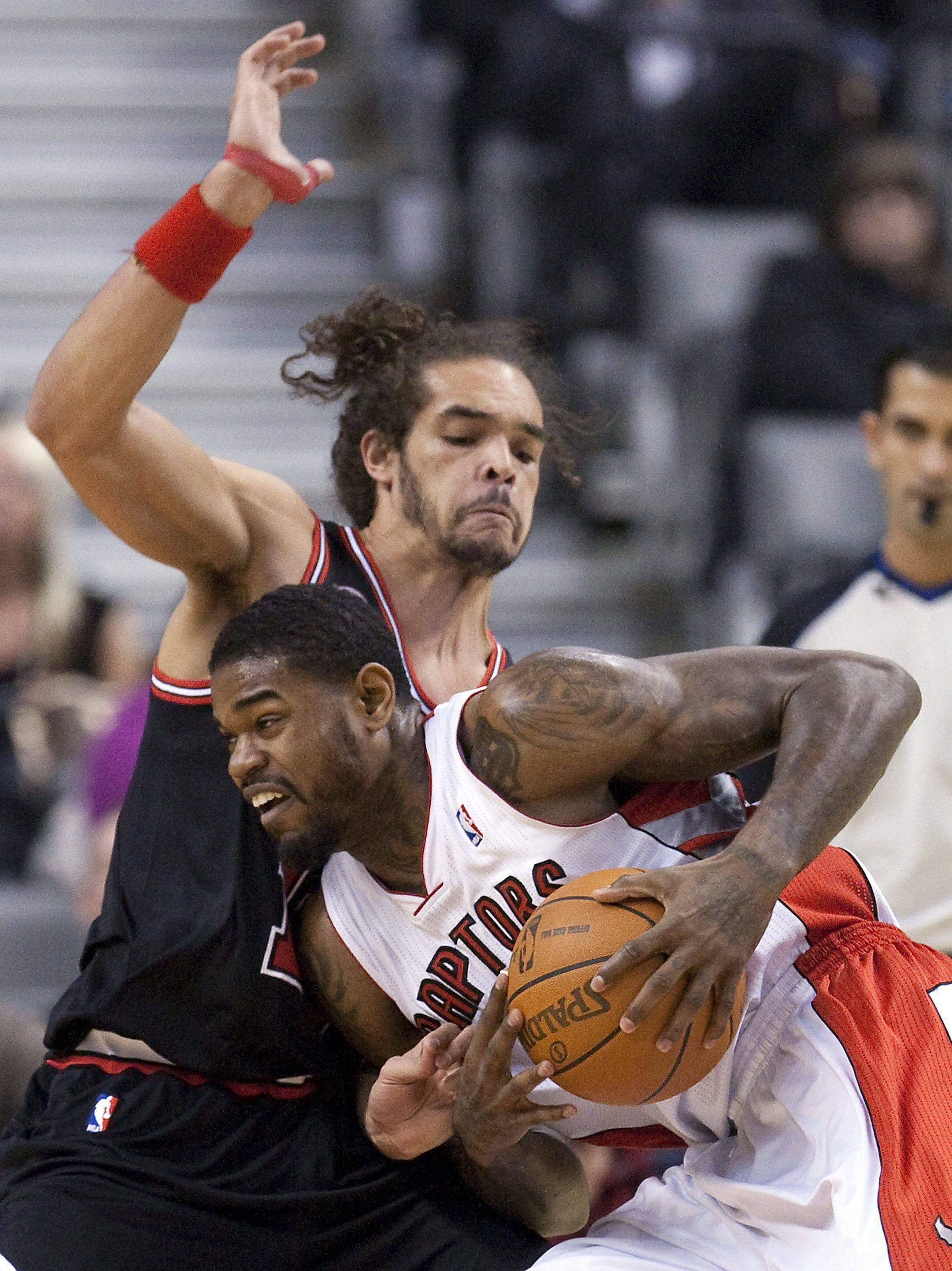 Bulls center Joakim Noah, with his right thumb wrapped, defends against the Raptors' Amir Johnson on Wednesday night. Noah finished with 11 points and 11 rebounds in his last game for a while.