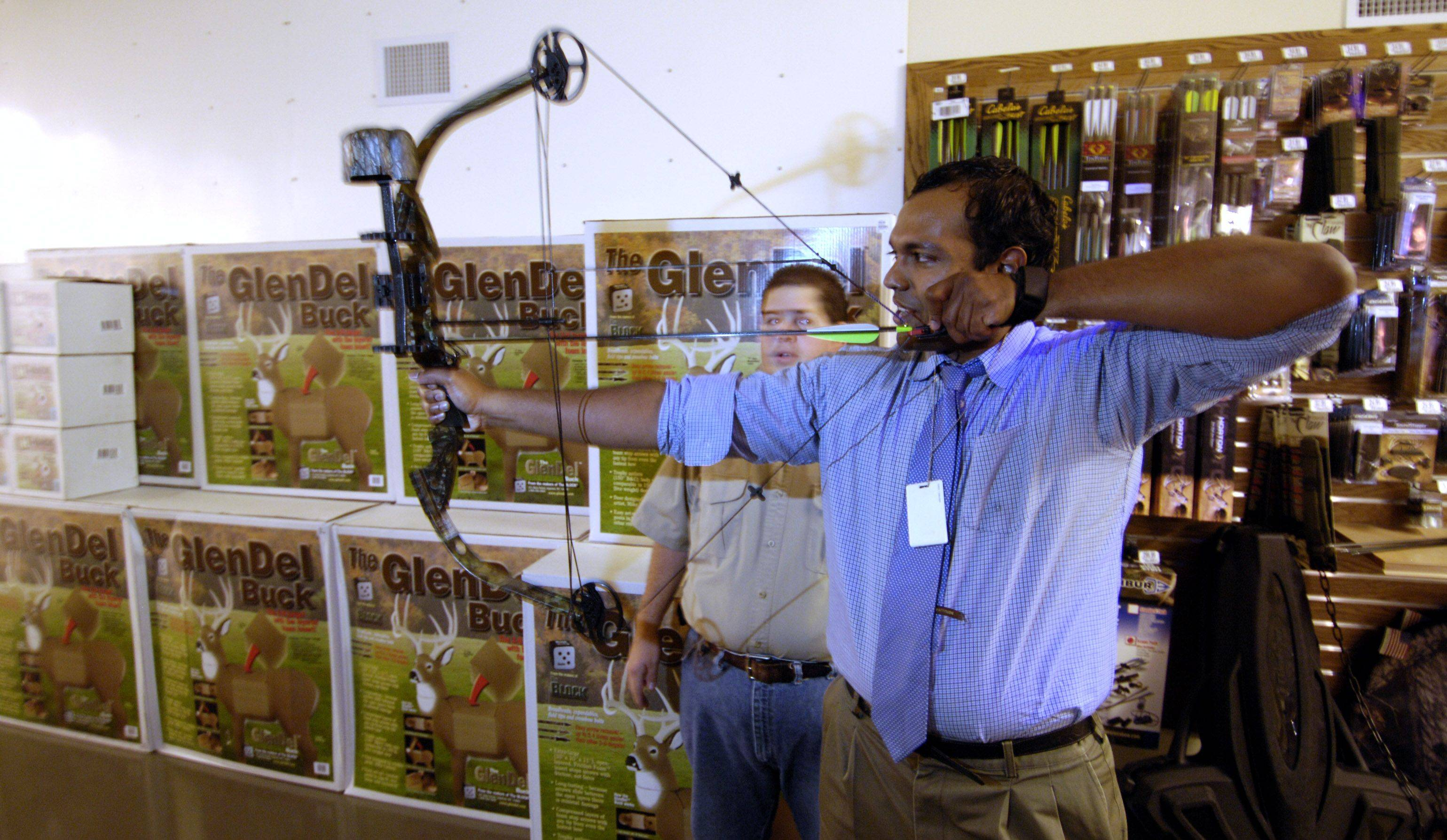 The use of compound bows, like the one being fired here by Daily Herald reporter Ashok Selvam, could soon be illegal in the village of Mount Prospect. Village officials are considering a ban after receiving calls from residents wanting to fire the powerful weapon outside their homes.