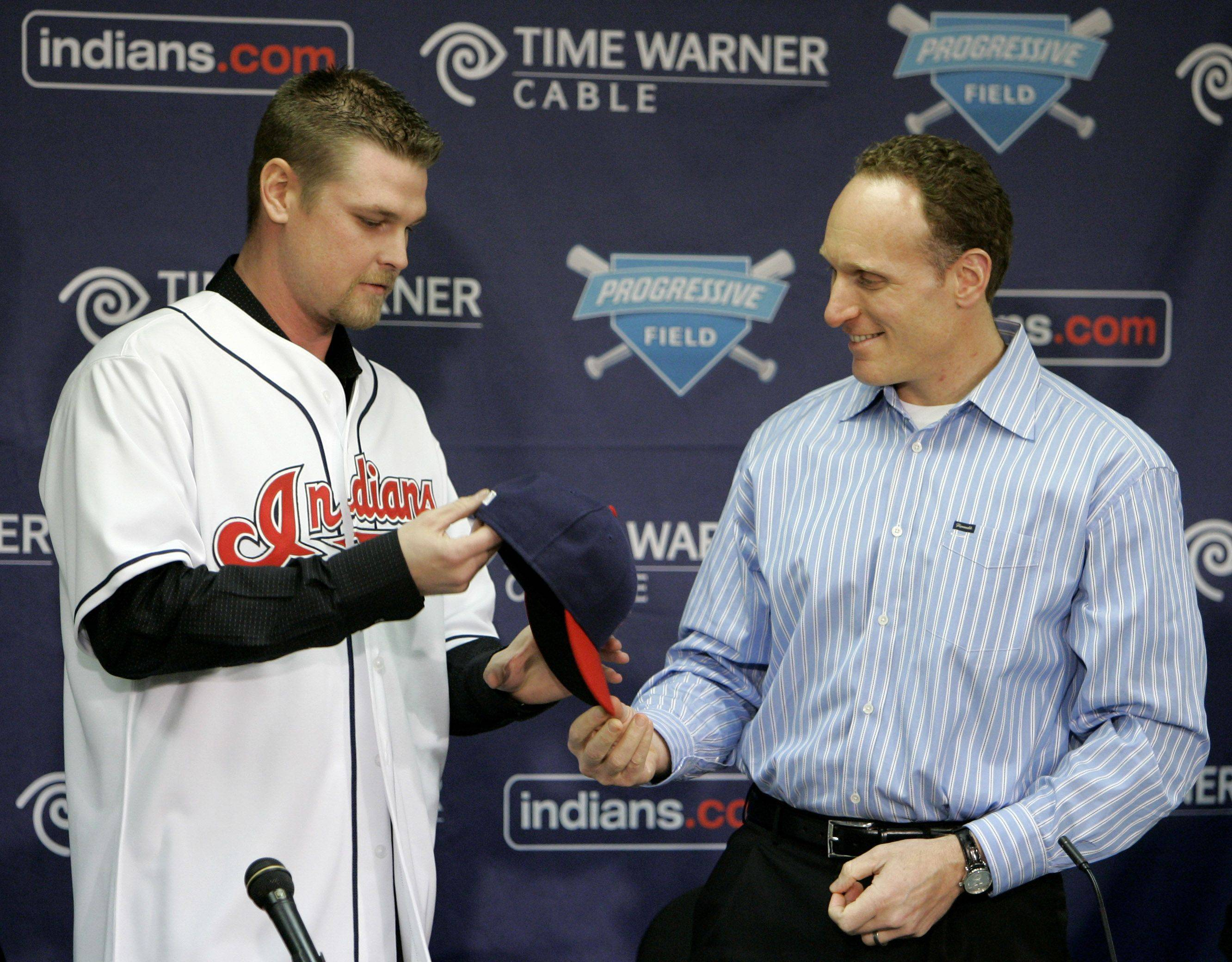 Pitcher Kerry Wood tries on his new Cleveland Indians jersey and hat with general manager Mark Shapiro Thursday, Dec. 18, 2008, during a news conference in Cleveland. Wood got his first look at at his new home ballpark after signing a two-year, $20 million contract with the Indians.