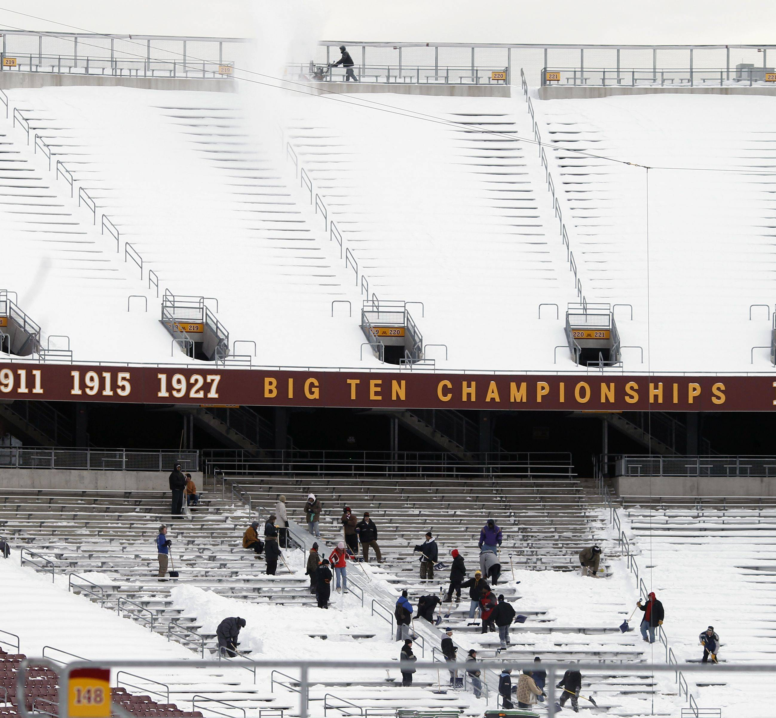 Work crews remove snow from the stands at TCF Stadium, home of the University of Minnesota football team on Wednesday in Minneapolis. The Minnesota Vikings decided to hold Monday night's NFL football game against the Bears at TCF Bank Stadium, but players are concerned the field will be frozen.