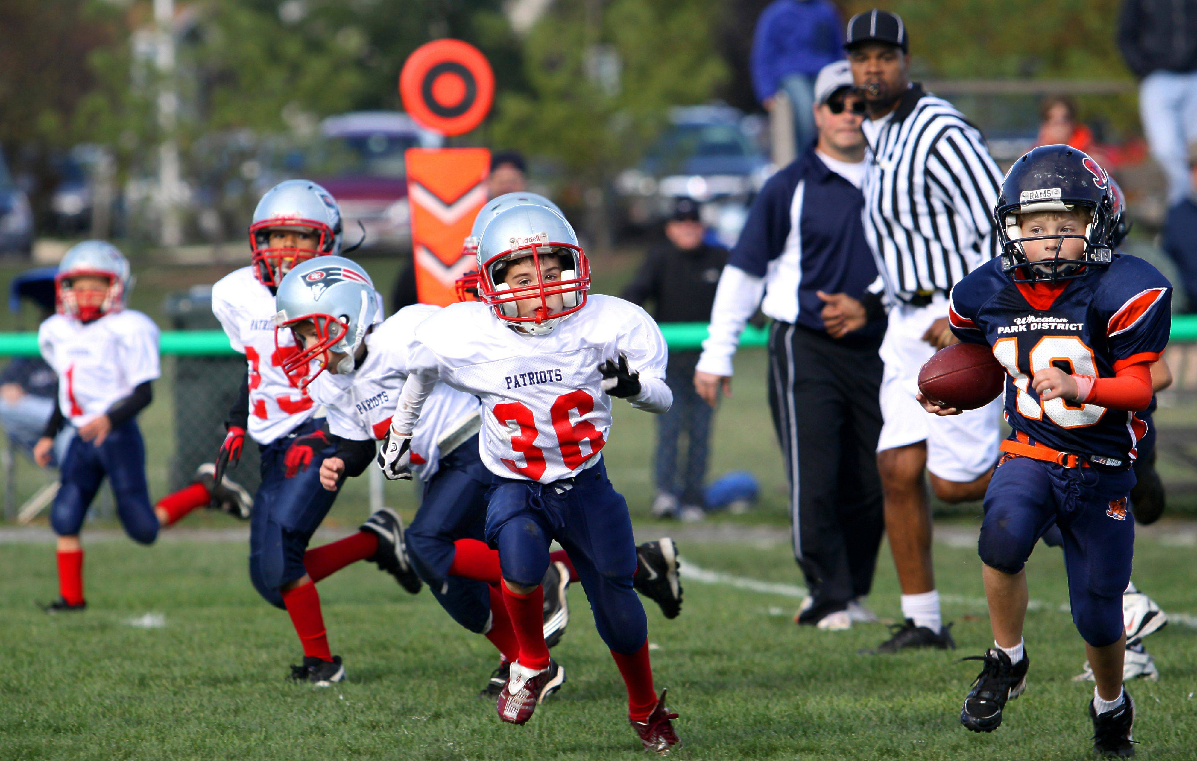 Young football players race down the field during a South Elgin Patriots football game.
