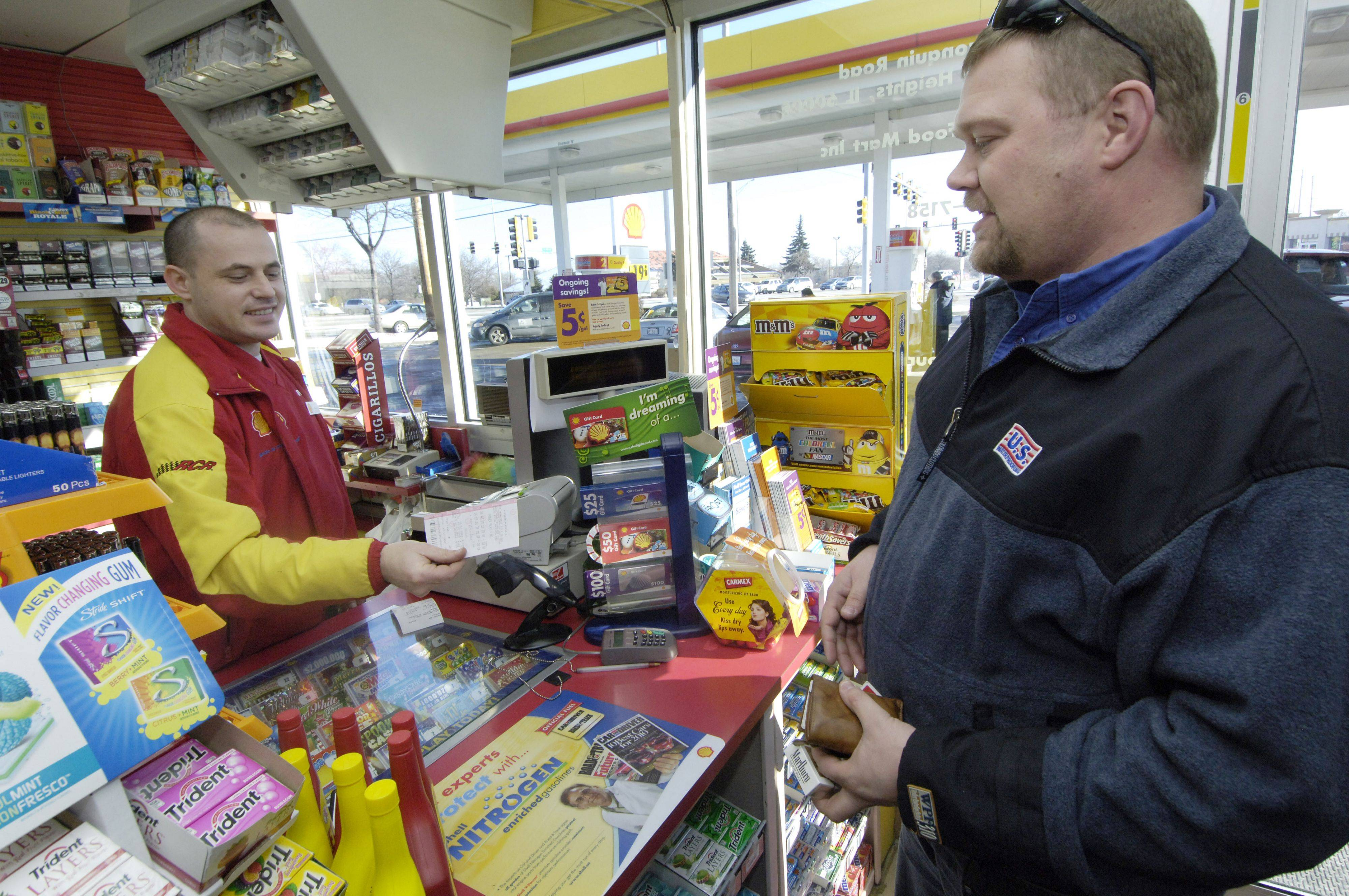 Kenneth Kirchner purchases a Powerball ticket from clerk Slavisa Miladinovic at the Arlington Heights Shell station at Arlington Heights and Algonquin roads Friday. Kirchner resides in New Lenox and works in Rolling Meadows.