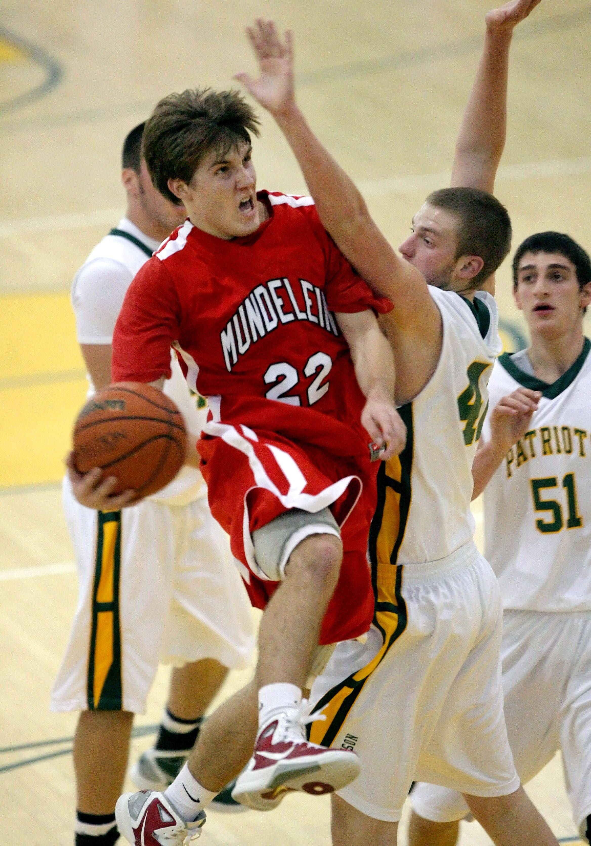 Mundelein's Robert Knar, left, drives past Stevenson's Brian Carlson during their game Friday night at Stevenson High School.