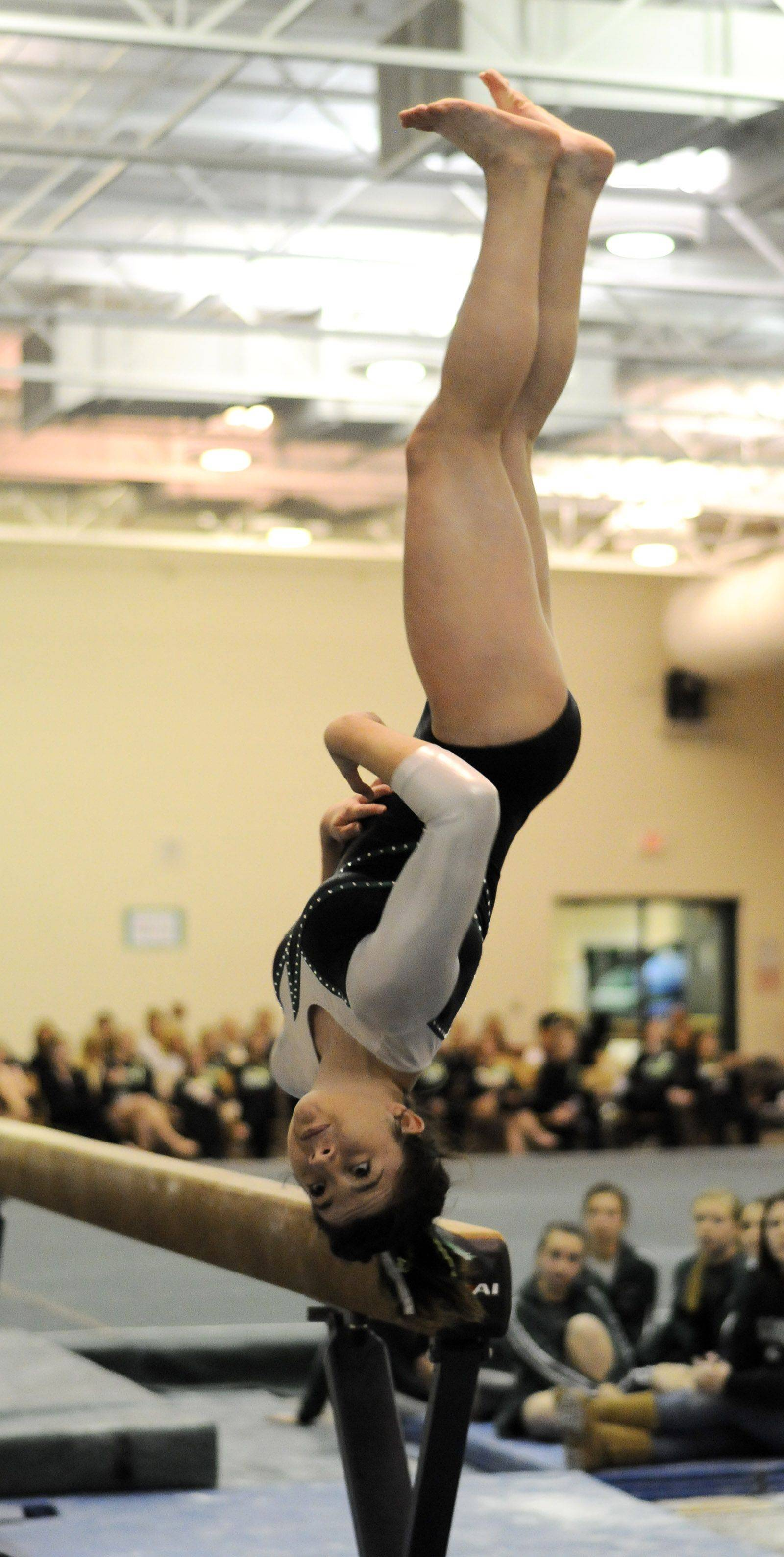 Glenbard West's Missy Guzman dismounts from the balance beam during the York at Glenbard West girls gymnastics meet.