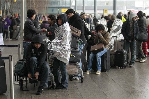 Passengers line as they wait to check-in for their flights outside Terminal 3 of Heathrow Airport in London, Tuesday.