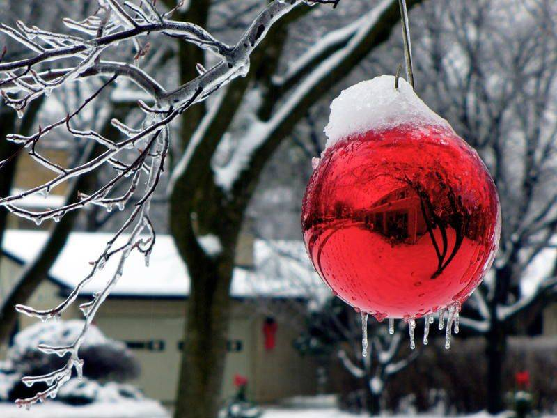 Reflection of a house is seen in a holiday ornament hanging on a tree after ice storm last December.