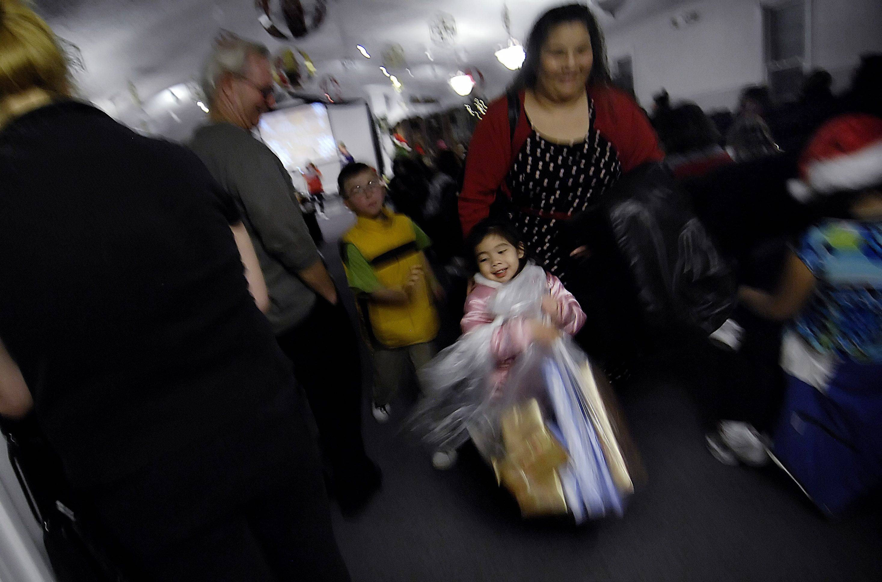 "Four-year-old Lily Parra happily leaves with a bag of gifts with her mother, Noel of Carpentersville. More than 100 families in need received a large bag of toys at The Carpenter's House Community Church's ""Toys 4 Kids"" program."