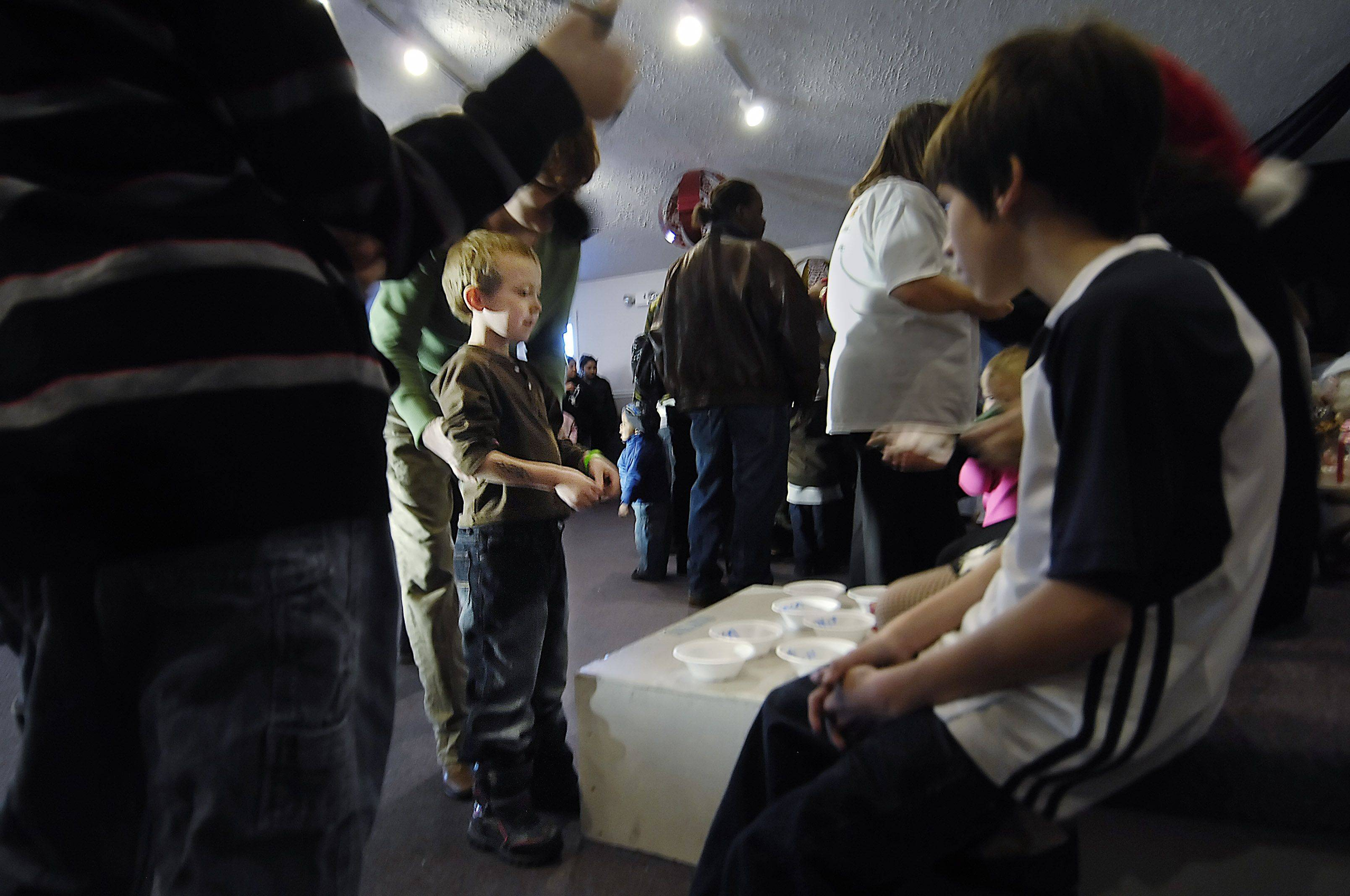 "A young boy approaches the raffle table during The Carpenter's House Community Church's ""Toys 4 Kids"" program. Many children won an extra raffled toy and everyone got candy."