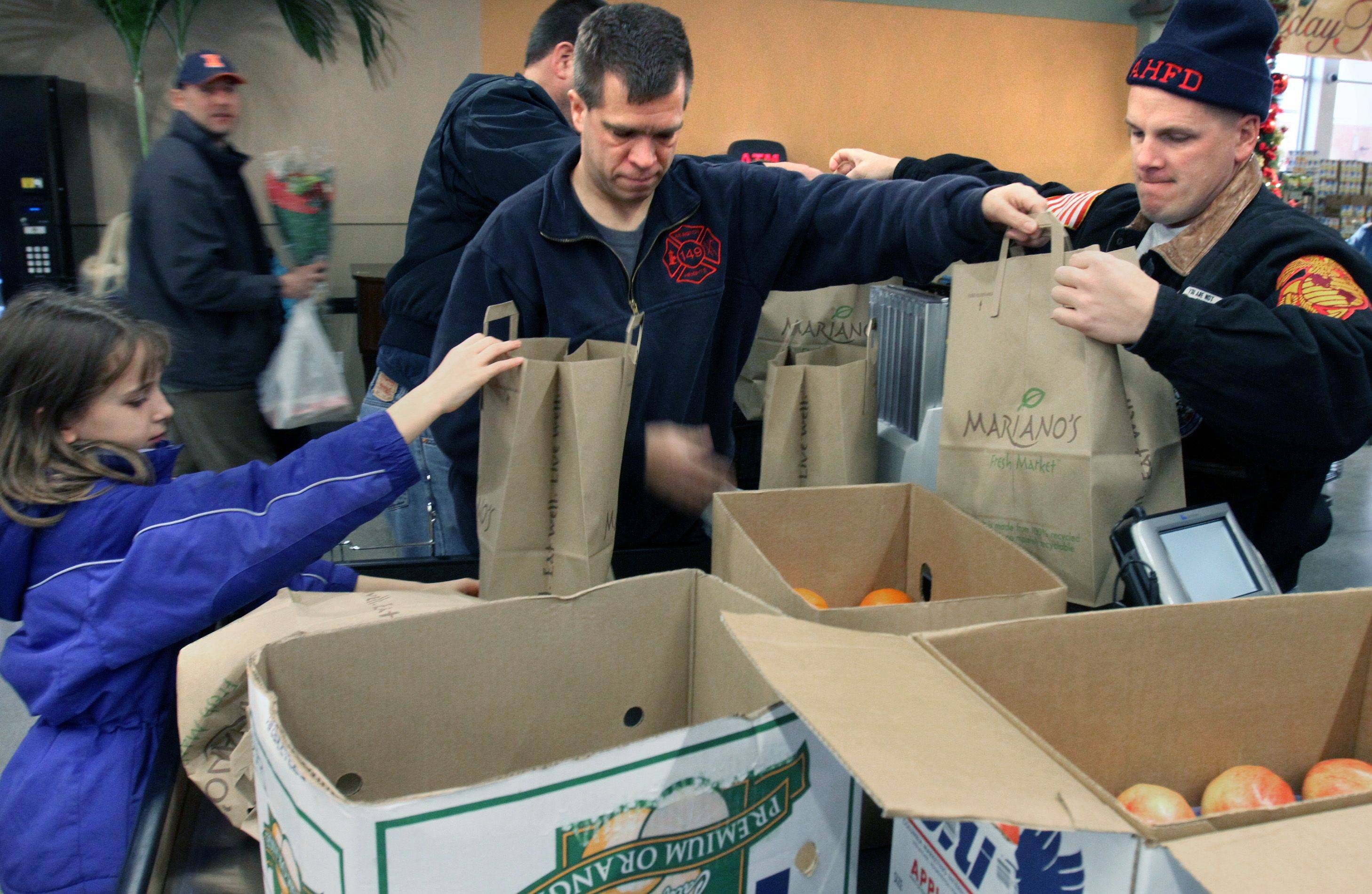 Arlington Heights firefighter EJ Mampe, right, and firefighter Stu Kuhn, center, and his daughter Abbey, 8, pack up bags filled with complete holiday meals at Mariano's Fresh Market in Arlington Heights Christmas Eve.