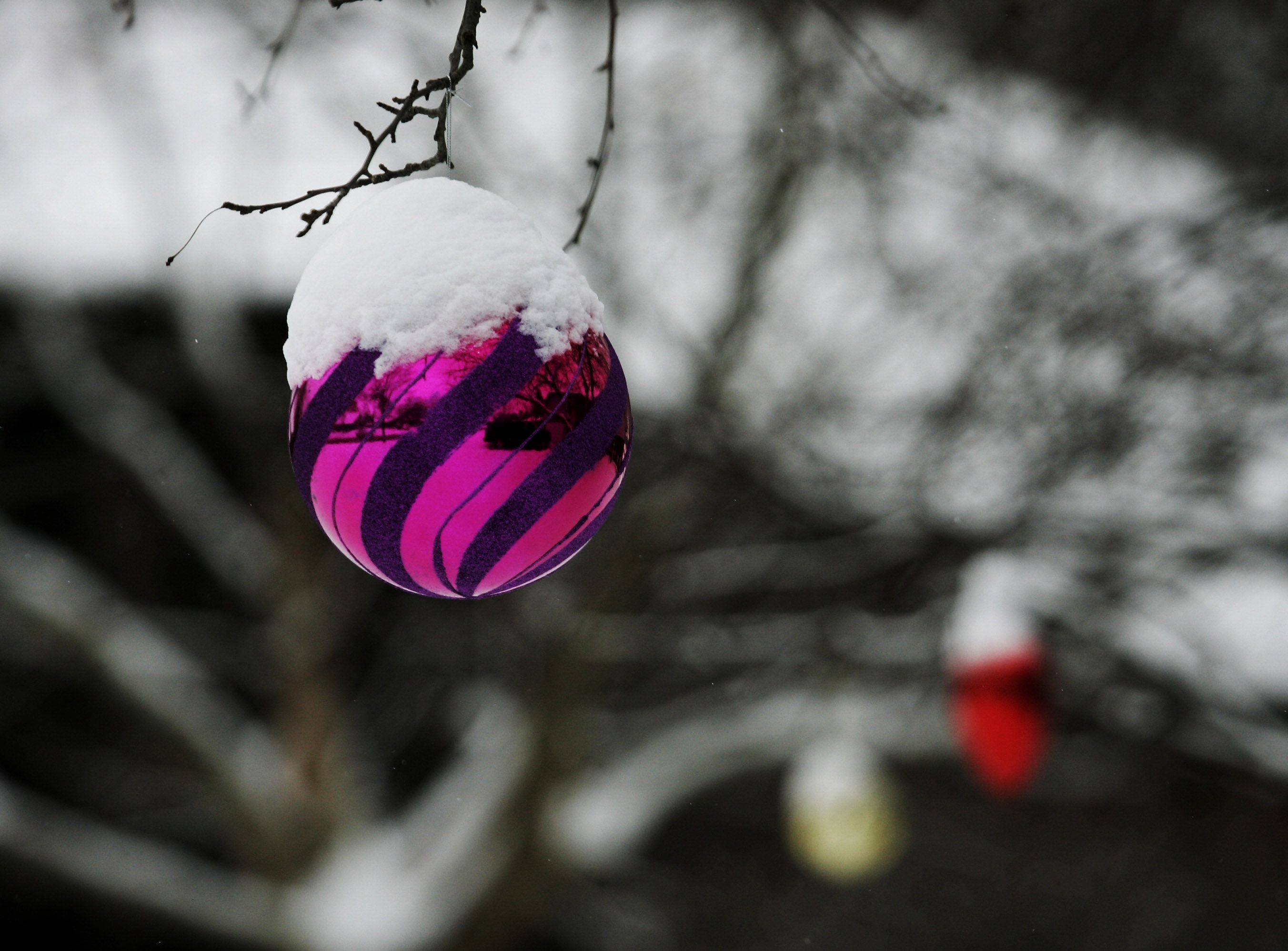A holiday ornament is covered in snow on a home along Home Ave. on Christmas Day in Palatine.