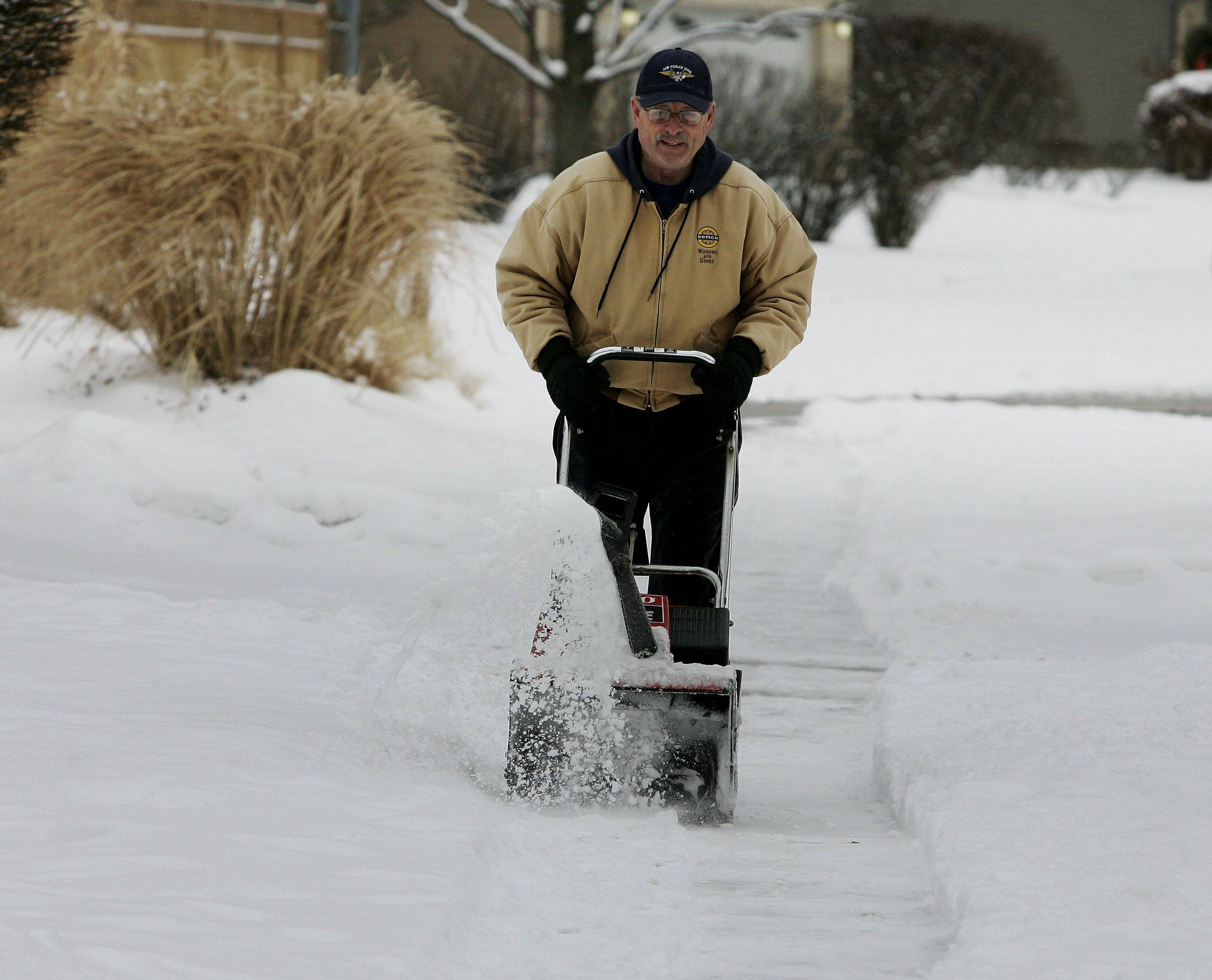 "Terry Countryman snow plows his neighbor's sidewalk along Garden Ave. in Palatine Christmas Day. ""My Christmas present this year was the snow,"" said Countryman. ""I hate the cold but I love the snow."""