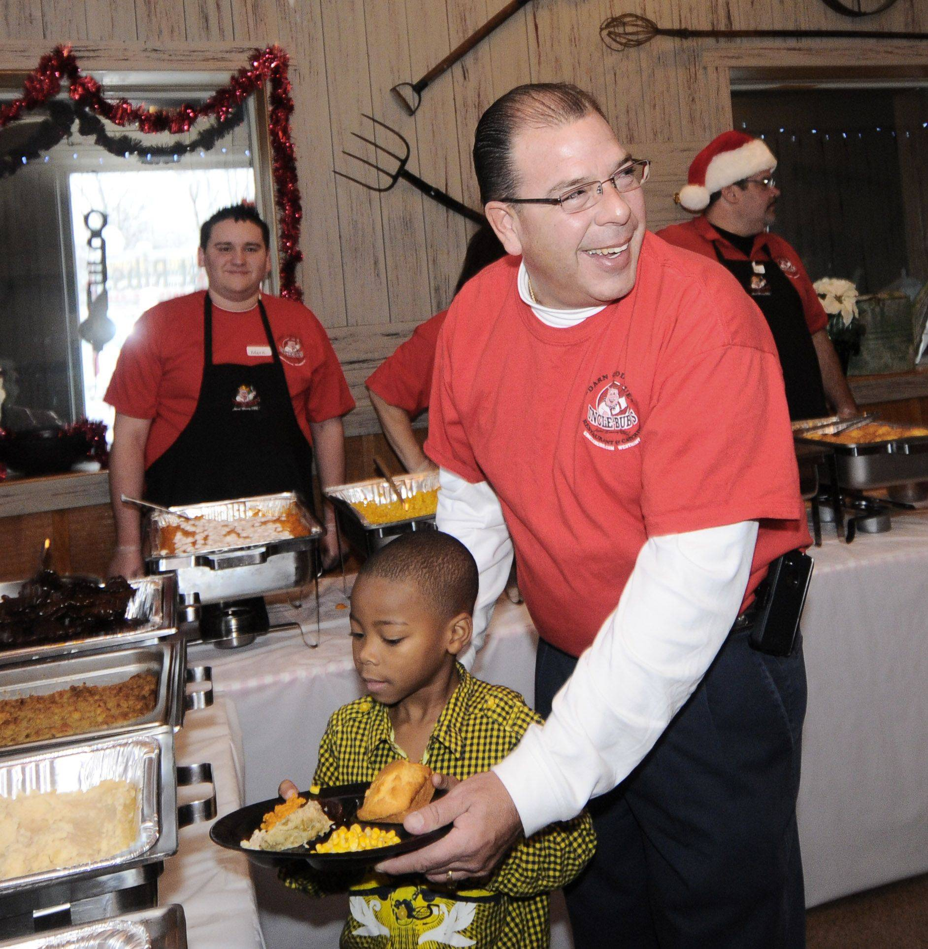 Mark Link, owner of Uncle Bub's Restaurant in Westmont, helps Tony Martin Jr., of Westmont, make his selections during Christmas day buffet which was proviede to 300 people at his restaurant.