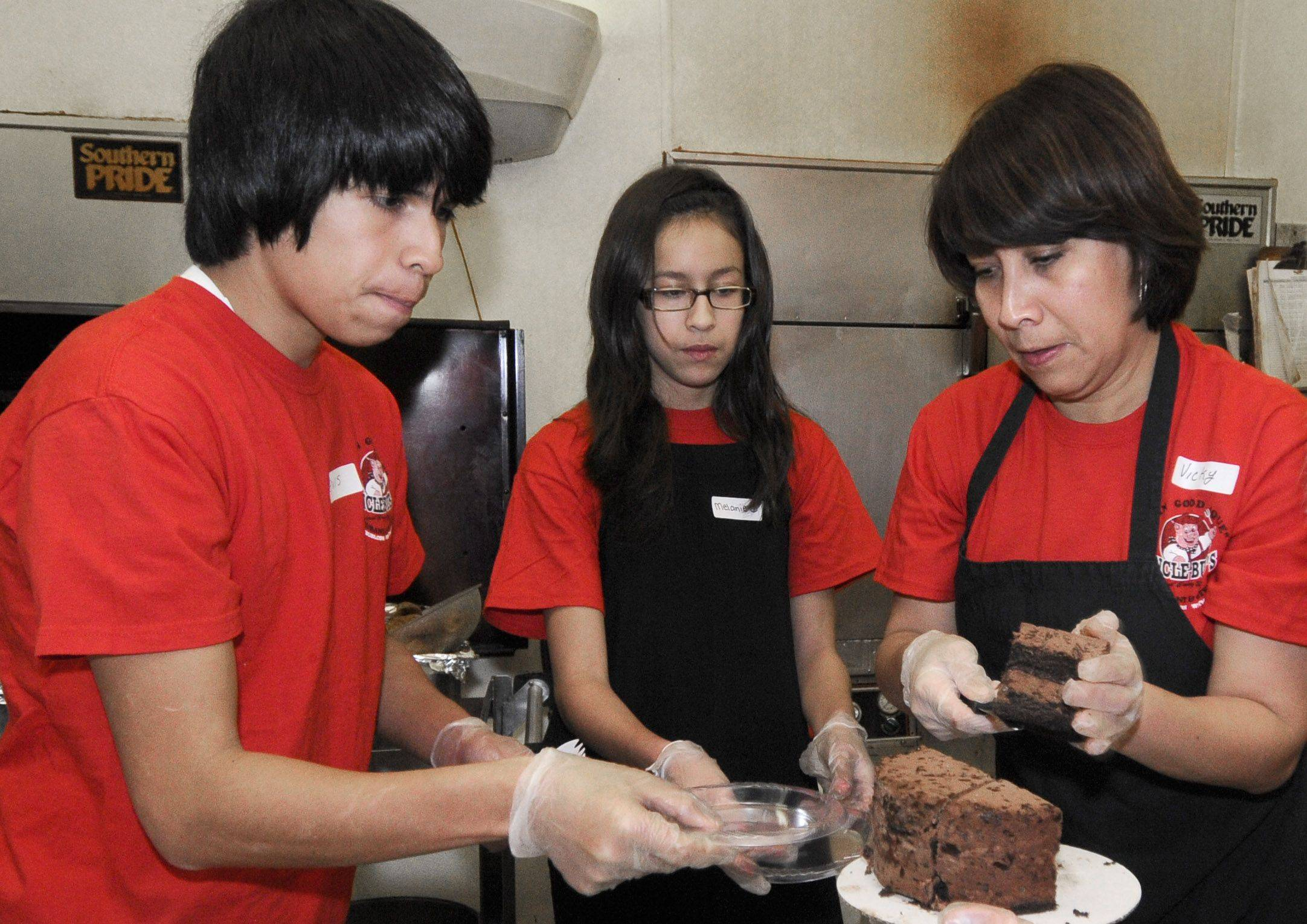 Restaurant employee Vicky Cordova, right and her children Elvis Barrios, left, and Melanie Barrios, center volunteer their time to get the desert cakes ready to serve at Uncle Bub's restaurant in Westmont Christmas day.