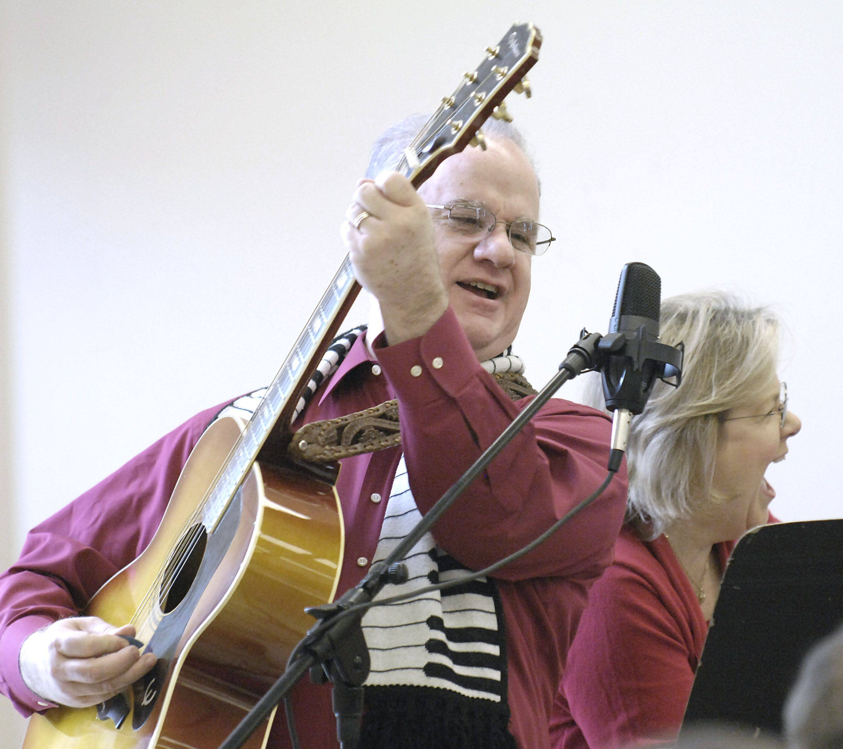 Charlie Brown and his wife, Alice, of Geneva finish a version of Rudolph the Red Nosed Reindeer with gusto at the annual Christmas brunch at Lazarus House in St. Charles Saturday.