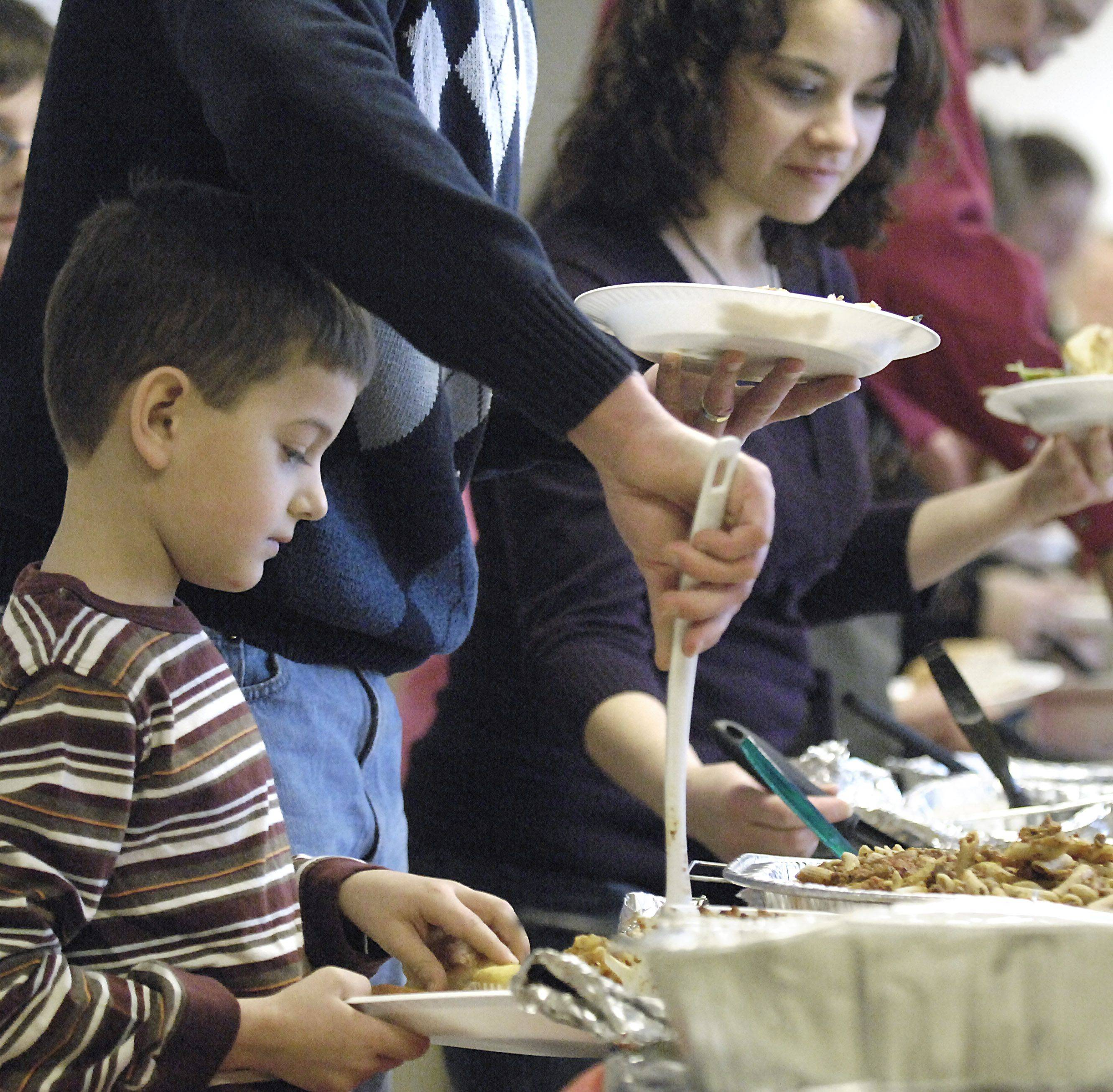 Cole Hemmes, 7, of Batavia gets help from dad Kimo Hemmes while filling his plate at the annual Christmas brunch at Lazarus House in St. Charles Christmas day.