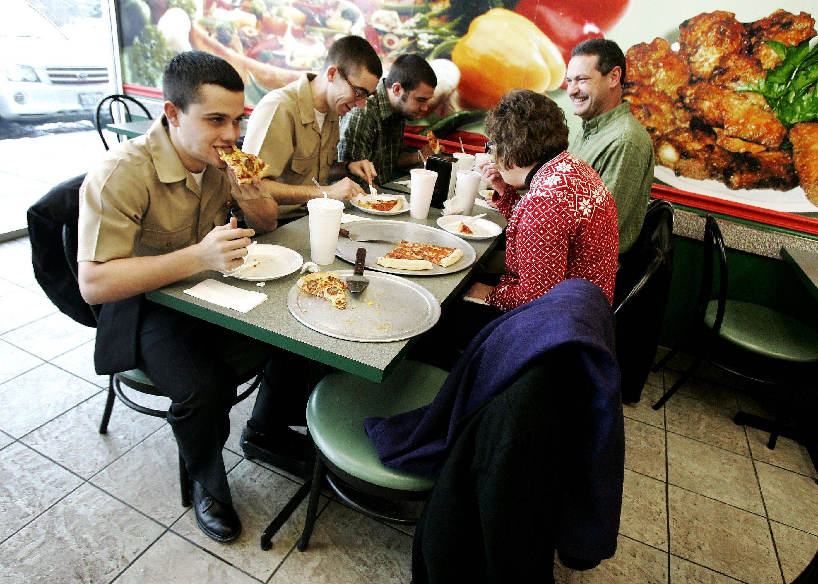 Pedro Santana, left of Houston, Texas, joins the Radcliff family from Ohio from left, Brandon, Ryan, Debbie, and Bob as they enjoy pizza for lunch at Sarpino's Pizzeria in Riverwoods. The family was participating in the Adopt-A-Sailor program from Great Lakes Naval Base on Christmas Day.