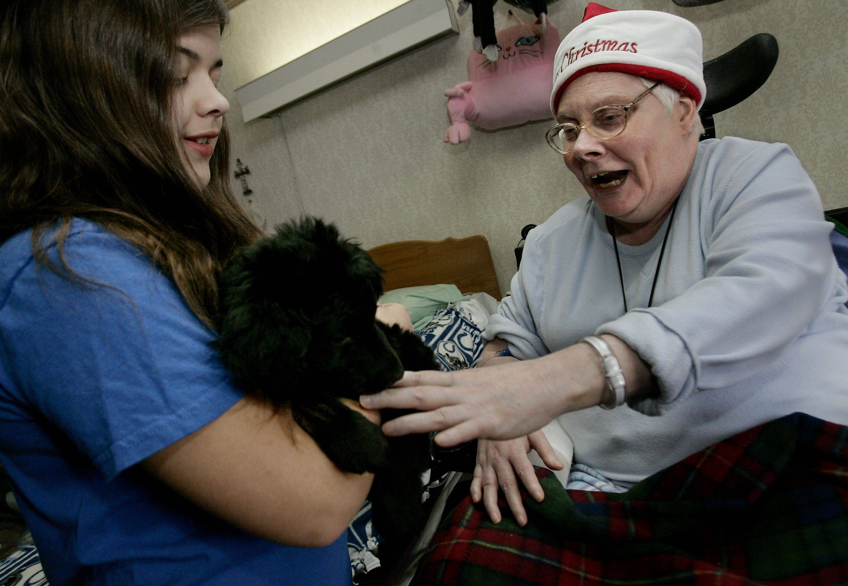 Manor Care resident Deb Brons, right, pets Josie, a special needs puppy, held by Lisa Severini, 12, of Gurnee as Libertyville's Animal Education and Rescue supporters brought their pets to greet residents in Libertyville Christmas Day.