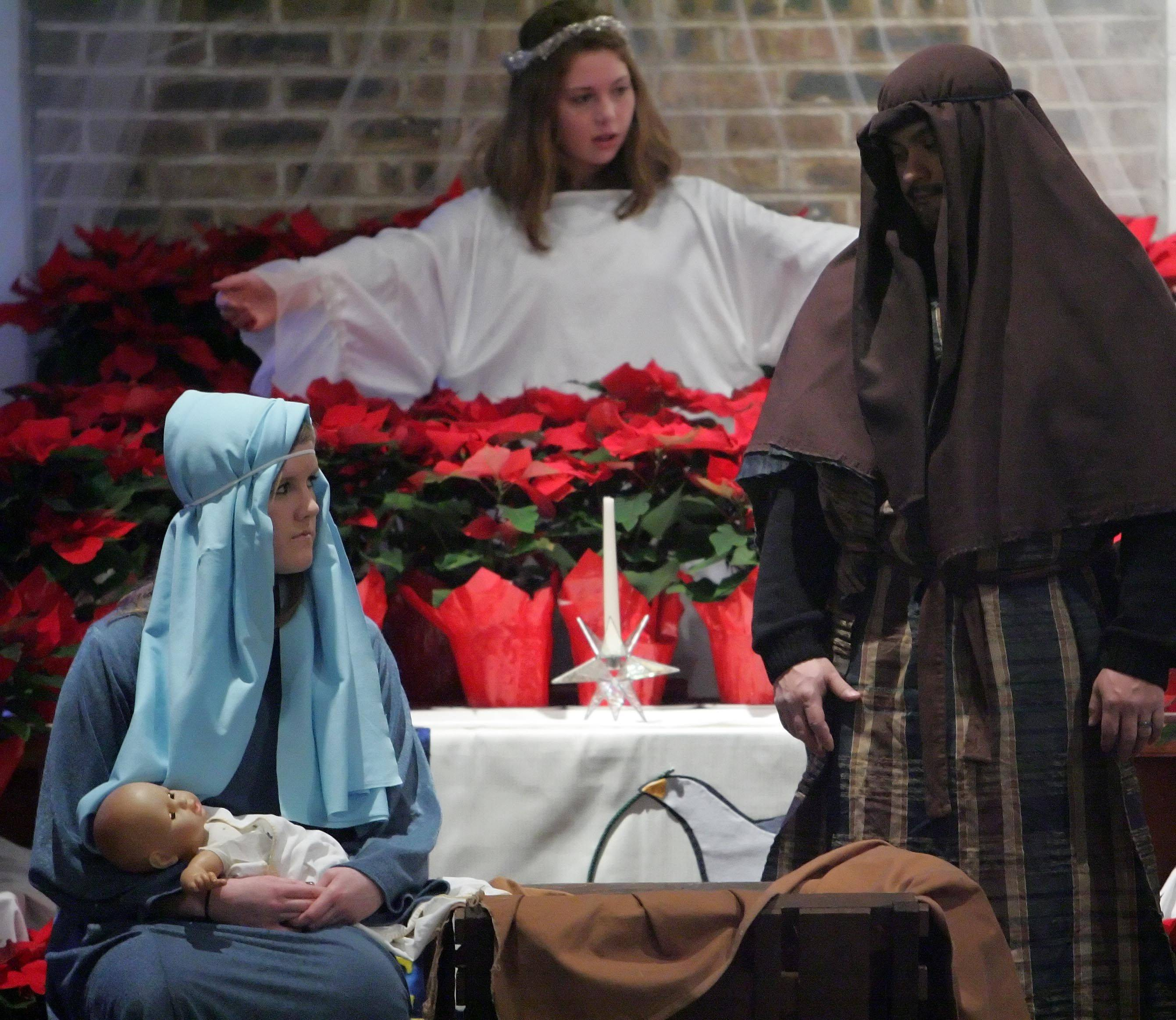 Maddie Loeffler, front left, portrays Mary, Josue Aguilar, portrays Joseph and Hannah Rose, portrays an angel in the living nativity scene at United Church of Christ in Arlington Heights Chrismtas Eve.