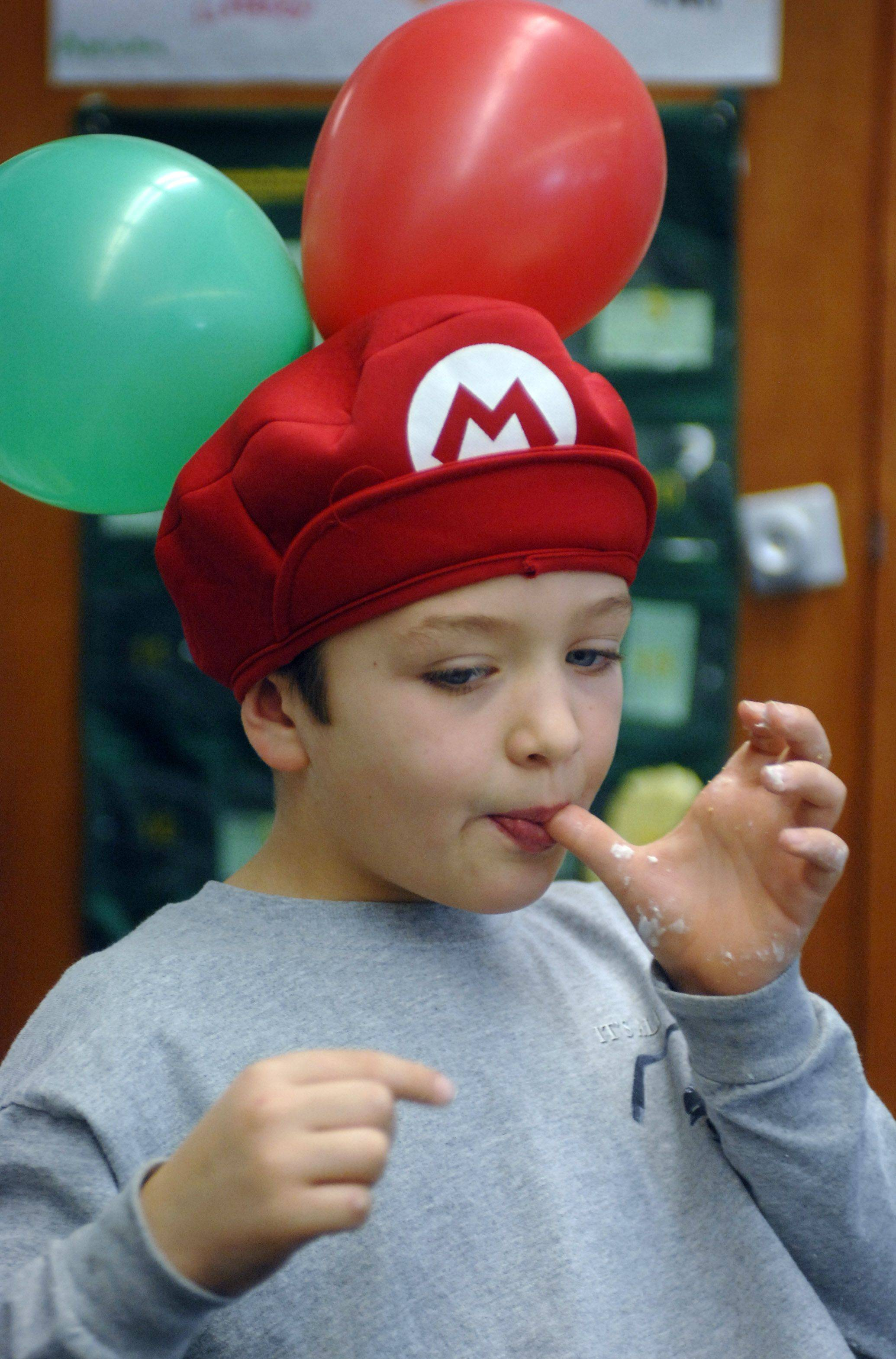 Adler Park School first-grade student Logan Hyatt takes a taste of frosting while he and fellow classmates made gingerbread houses Friday at the Libertyville school. First-grade students have been learning about winter holidays and reading gingerbread-themed books.