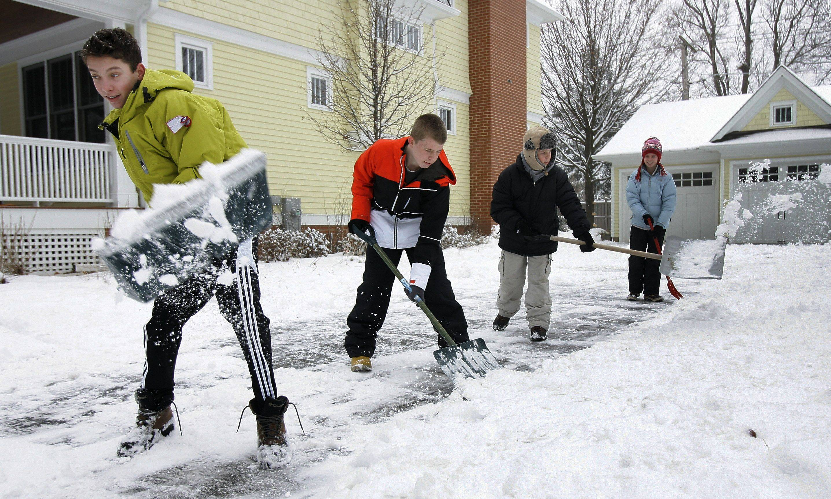 Siblings Jimmy Keefe, left, Connor Cleary, Ryan Cleary and Julia Cleary shovel the Cleary driveway on Carter Street in Libertyville Tuesday after snow fell overnight covering the Lake County area.