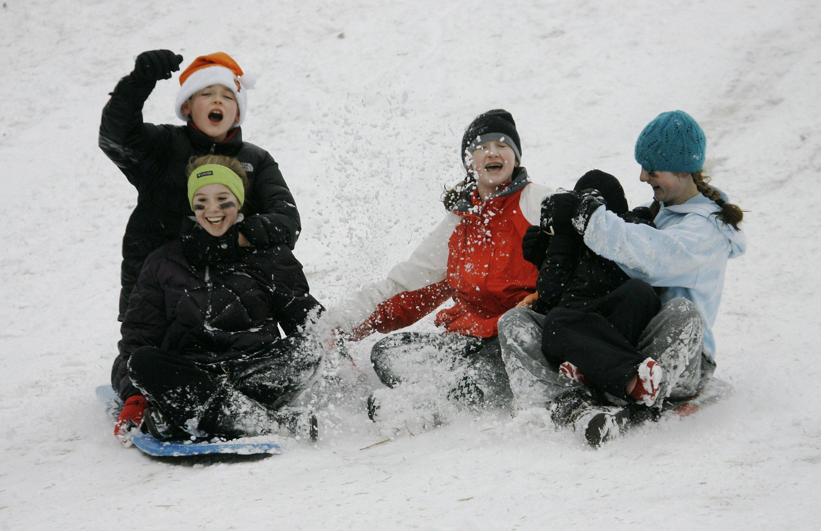 Michael Graham, 11, left, Morgan Burns, 13, Kelly Griffin, 12, Bridget Graham, 5, and Mary Graham, 12, hold onto each other as they go down the sled hill at Adler Park in Libertyville Tuesday.