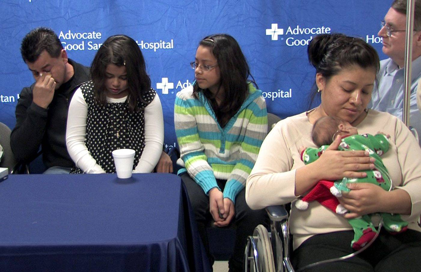 Martin Huerta, left, gets emotional while talking about the difficulties with the premature birth of his son Martin Huerta, Jr., right, on the lap of his mother Angelica Salas of Plainfield. They were able to bring the baby home in time for Christmas. He was born threee months premature at Advocate Good Samaritan Hospital in Downers Grove. In the center are sisters Brenda, 9 and Jasmine, 10, right.