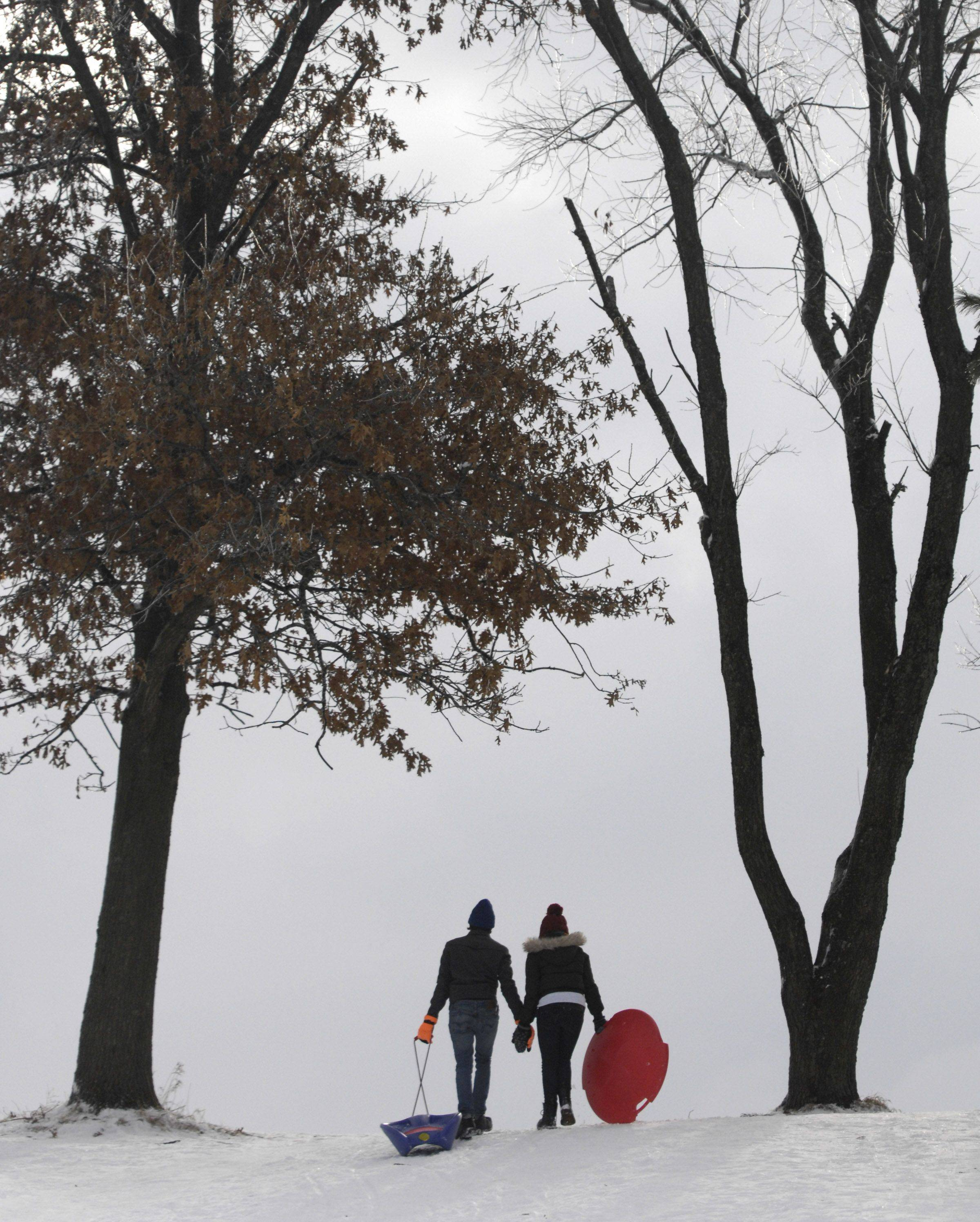Josh Graber of Carpentersville and Emily Caliende of Algonquin walk hand in hand as they climb the sledding hill at Randall Oaks in West Dundee.