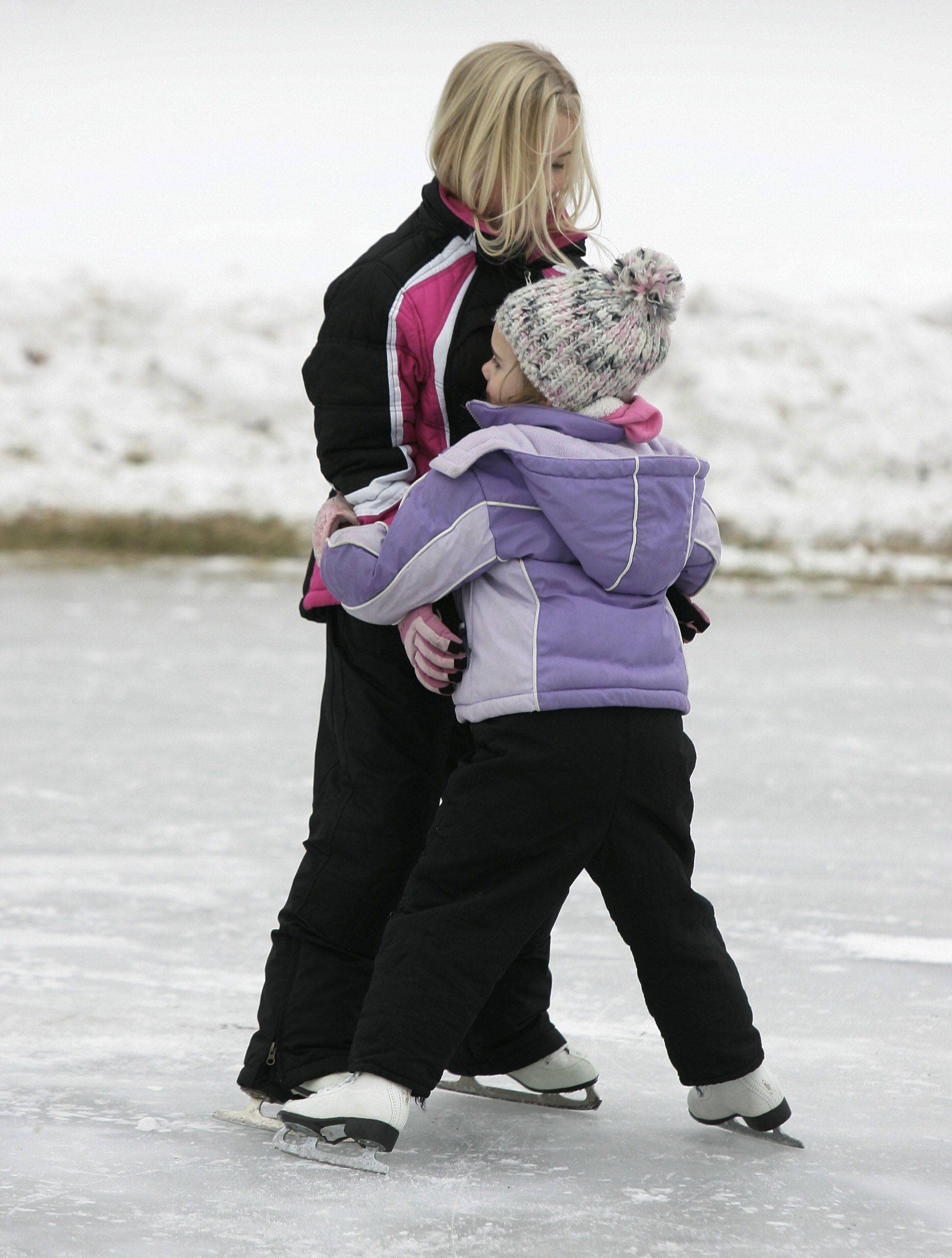 Paige Rankin, 8, of Libertyville helps her litle sister, Grace, 4, learn to ice skate at the ice rink in Nicholas-Dowden Park in Libertyville Tuesday.