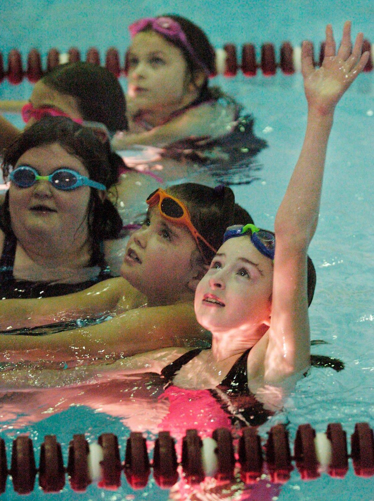 Katie Shaughnessy raises her hand to ask a question during Otters practice for the Arlington Heights Park District swim team.