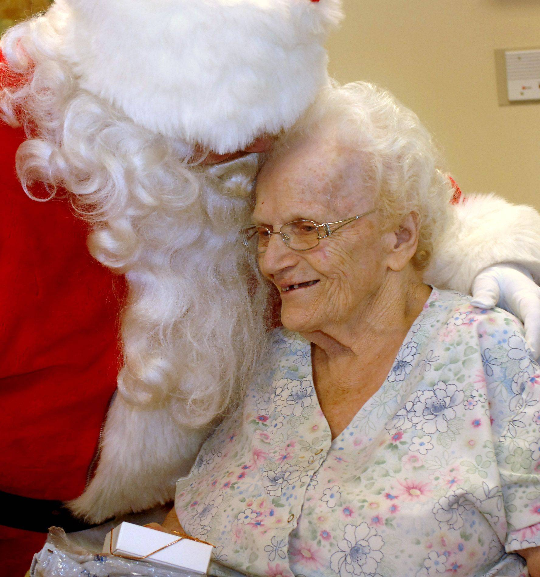 Santa gives a hug to Helen Hecketsweiler of Mundelein during his visit to Winchester House in Libertyville Wednesday during a holiday luncheon held for rehabilitation patients and a few longer-term residents.
