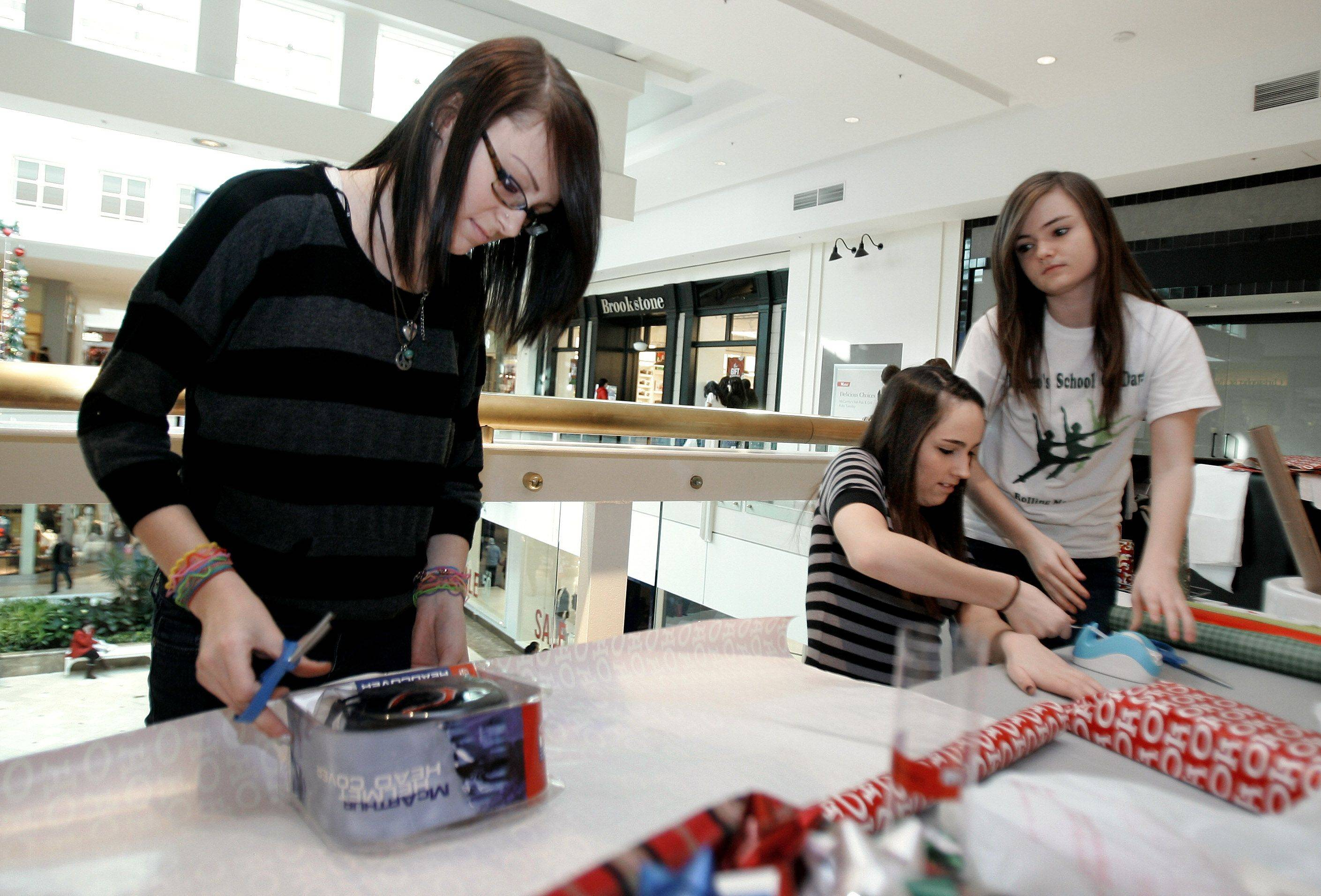 Tina Jordahl, 15, left, Kayla Suchomski, 15, and Caitlin O'Keefe, 16 all from Hoffman Estates, volunteer to wrap presents to raise money for the National Inclusion Project Wednesday at Westfield Hawthorn Shopping Center in Vernon Hills. The National Inclusion Project serves to bridge the gap that exists between young people with disabilities and the world around them.