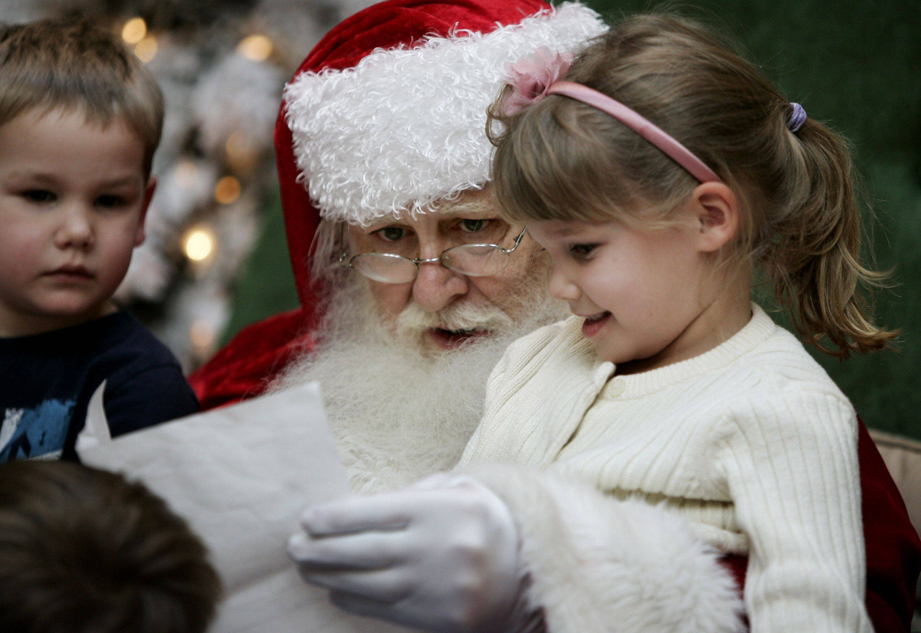 Santa Claus reads a Christmas wish list from Erin Casper, 5, of Wauconda while her brother Gavin, 3, looks on as Santa greets children at Westfield Hawthorn Shopping Center in Vernon Hills. Erin's list included markers, a Pillow Pet, and a purple, girl monkey.