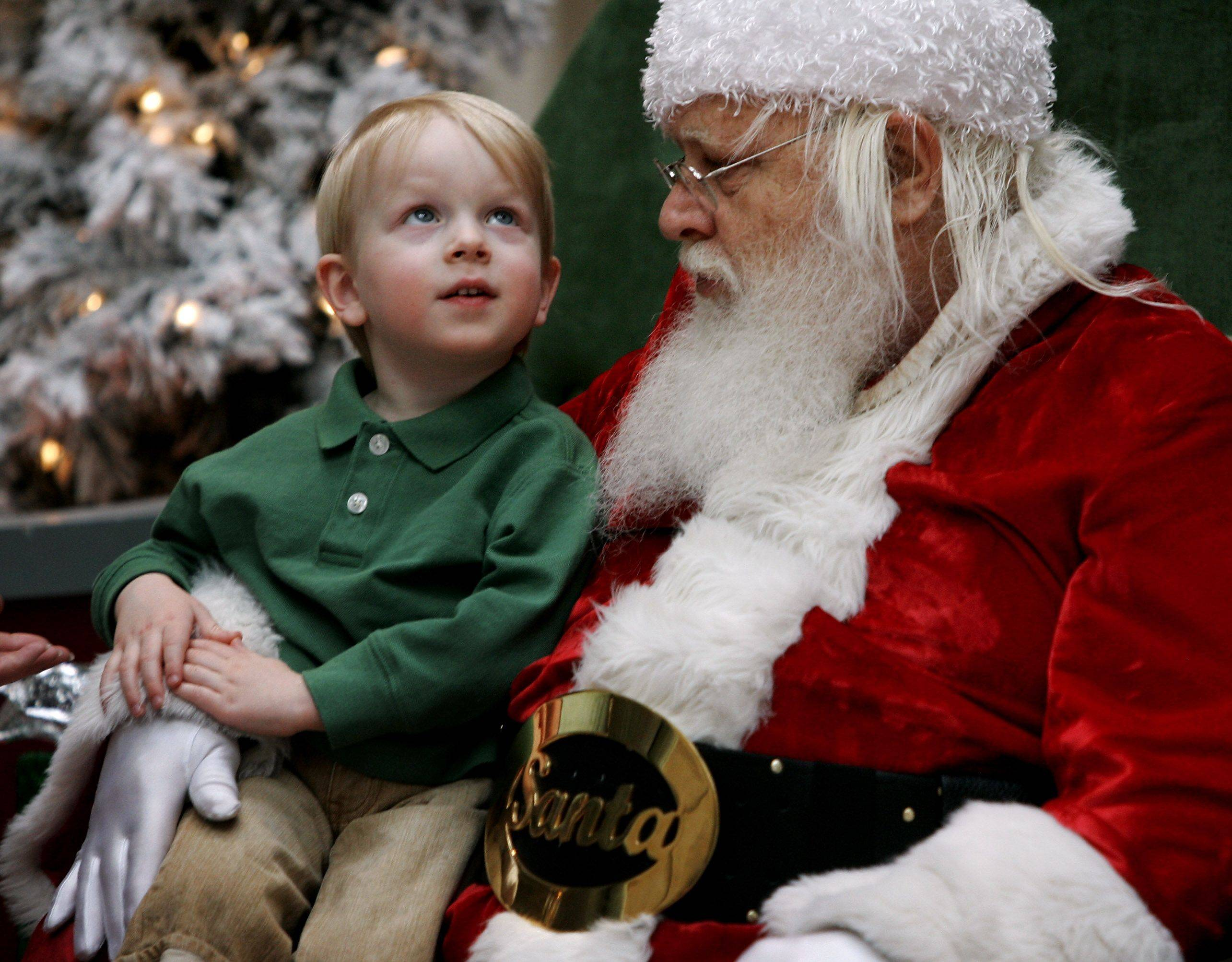Santa Claus listens to Owen Arnold, 3, of Riverwoods as he tells him what he wants for Christmas at Westfield Hawthorn Shopping Center in Vernon Hills.