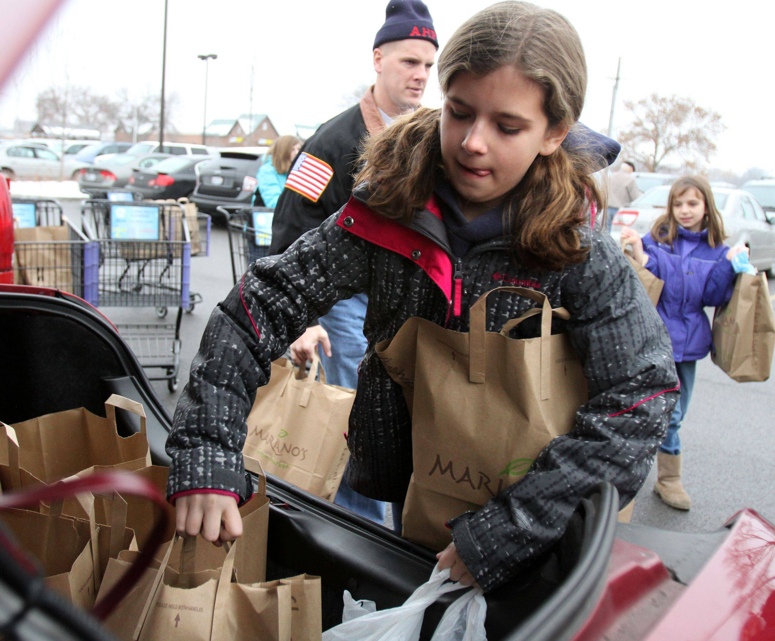 Katrina Kuhn, 11, of Arlington Heights, helps the Arlington Heights Fire Department, members of Local 3105, and fire department administration load large bags filled with complete holiday meals Christmas Eve for needy families.