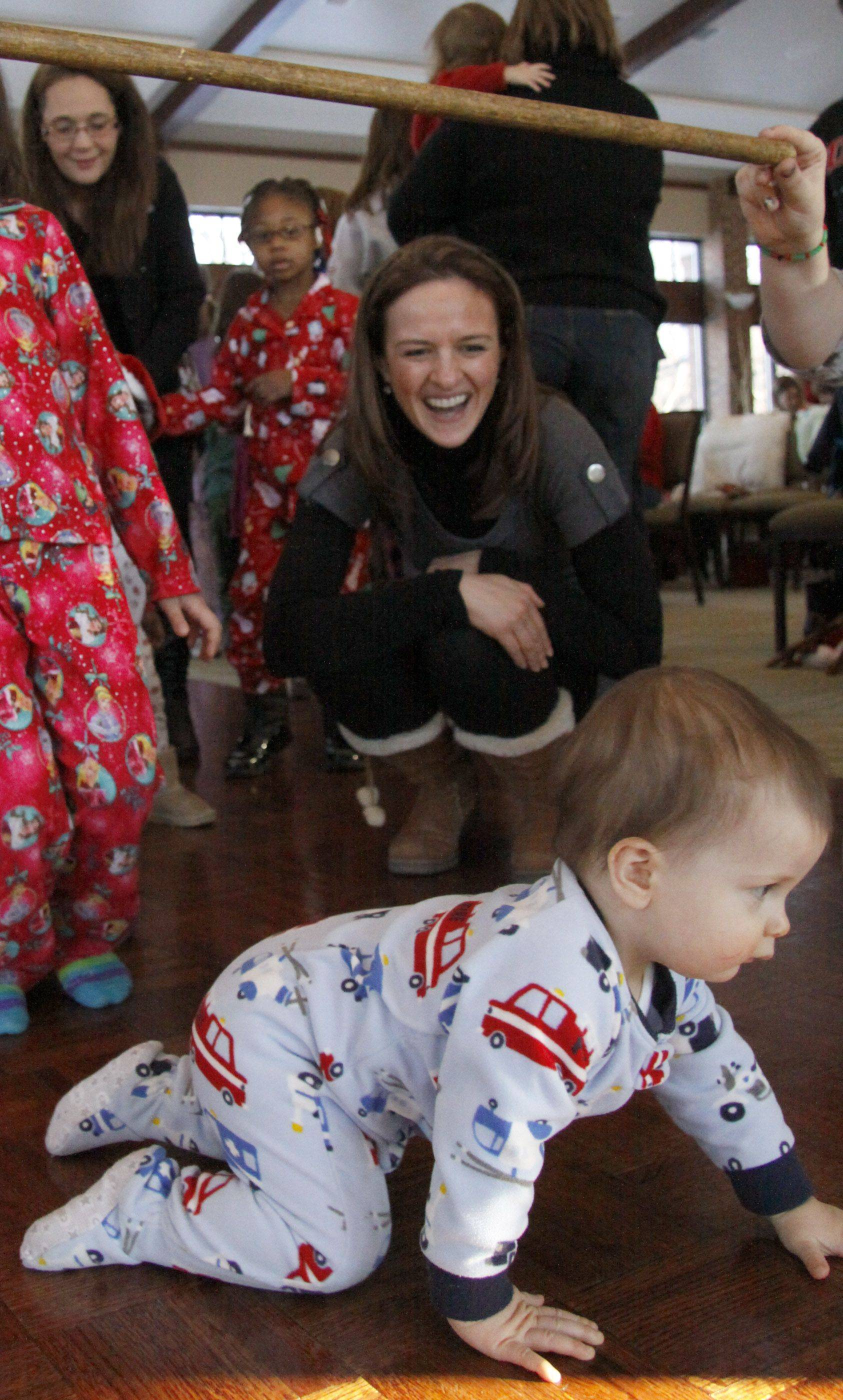 Ethan Stanescu, 10 months, crawls under the limbo stick while his mother Eliza Gryc of Aurora watches during the first Holiday Jammy Jam at Cantigny Park in Wheaton Saturday.