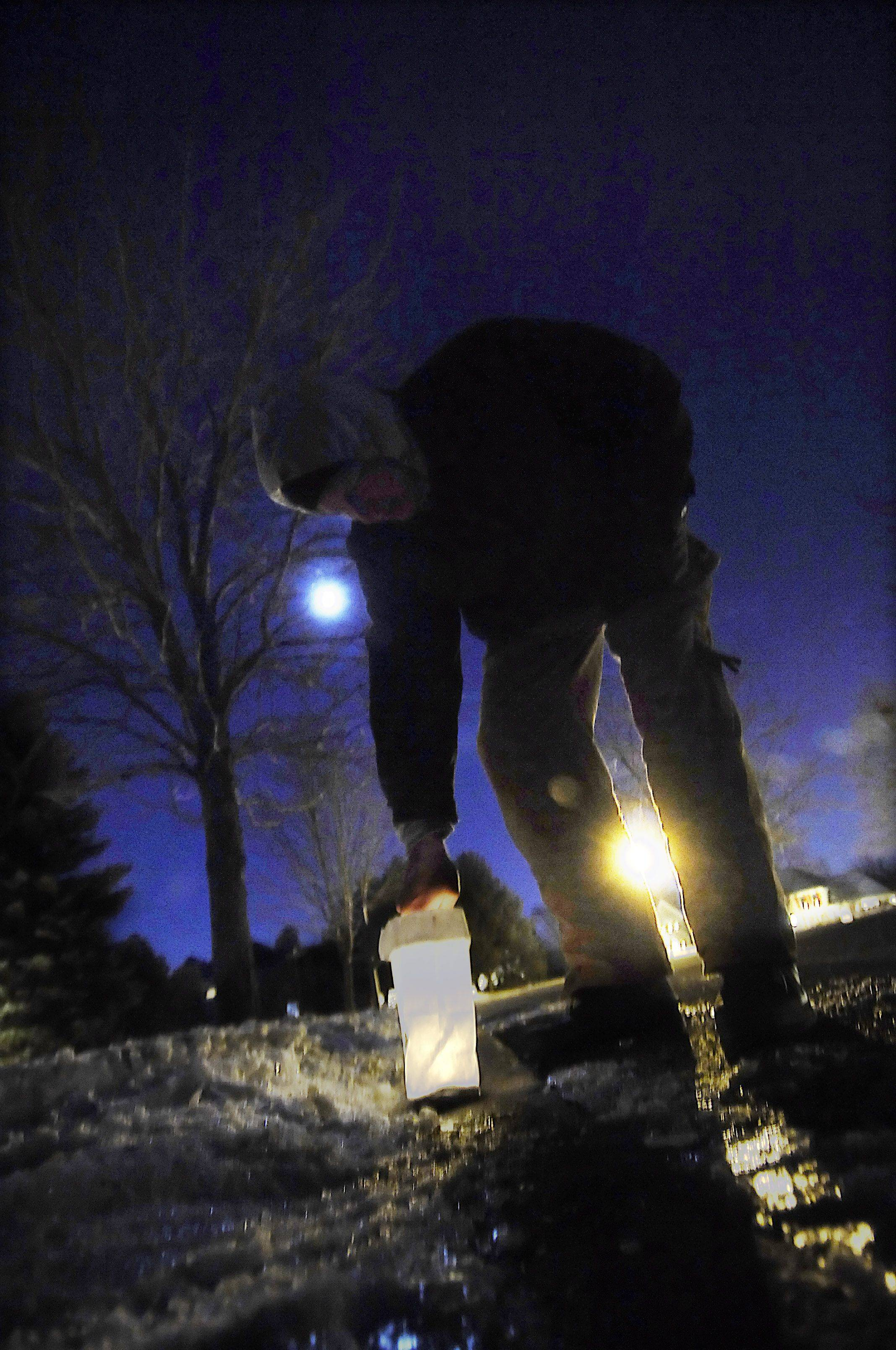 Randy Kohler lights luminarias in his yard Sunday night in the Patriot Meadows subdivision in Cary. He said he has been a part of the neighborhood glow since he moved there 18 years ago. Spruce Tree Drive is decorated with more than 1,200 luminarias.