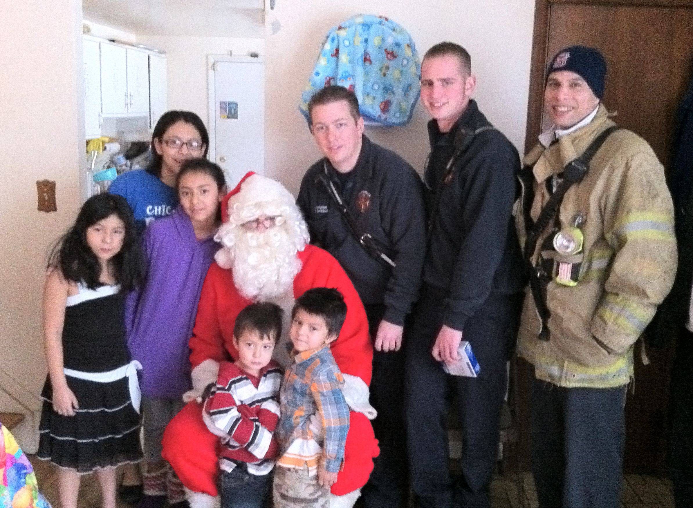 Photo courtesy of Carpentersville Firefighters Local 4790Carpentersville firefighters get a hand from Santa Claus while handing out gifts . Firefighters, from left, are Brian Simpson, Ben Foltin and Chris Bolliger.