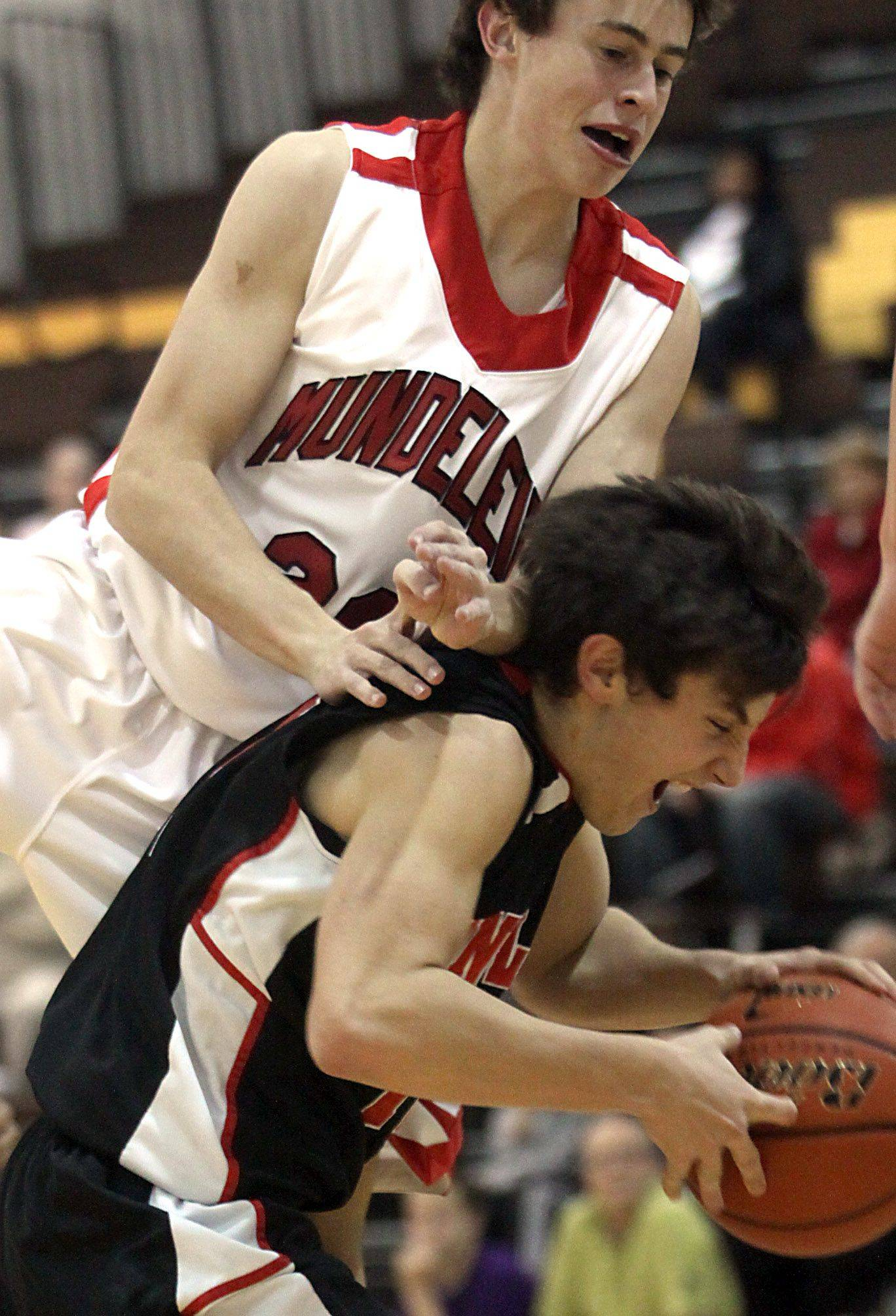 Jake Dachman of Huntley, bottom, tries to keep a handle on the basketball as Nate Brune of Mundelein plays defense during the title game of the Jacobs Holiday Classic Boys Basketball Tournament in Algonquin on Thursday night.