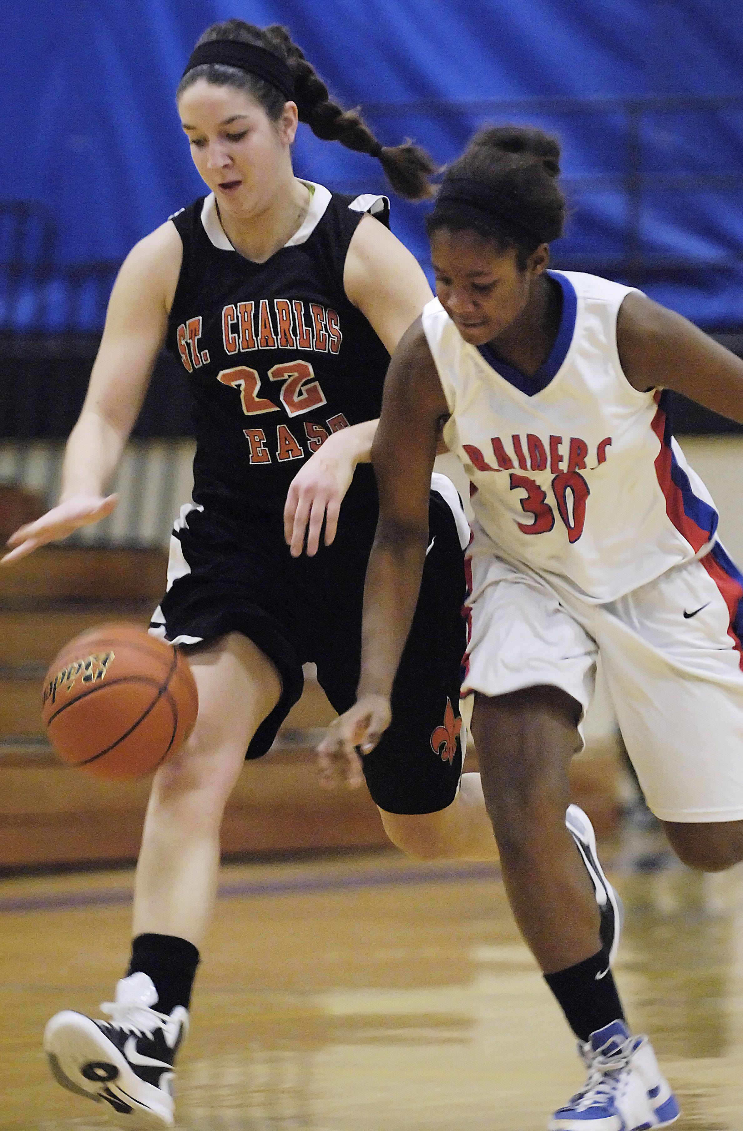 St. Charles East's Dani Asquini and Glenbard South's Hannah Davey chase a loose ball at the Wheaton North Holiday Tournament Monday.