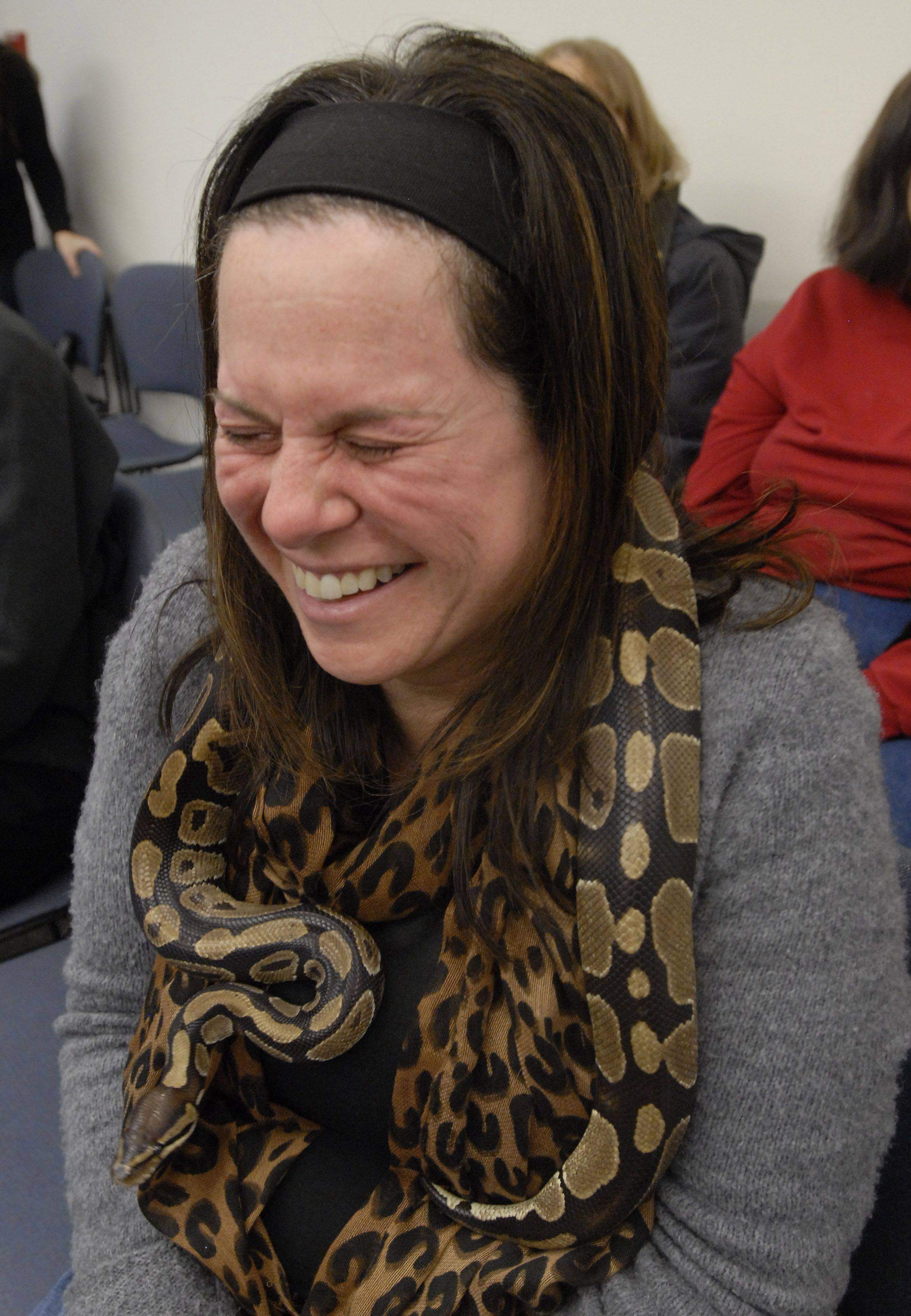 Jen Jacobs reacts to a python being placed on her neck Wednesday at Indian Trails Public Library in Wheeling.
