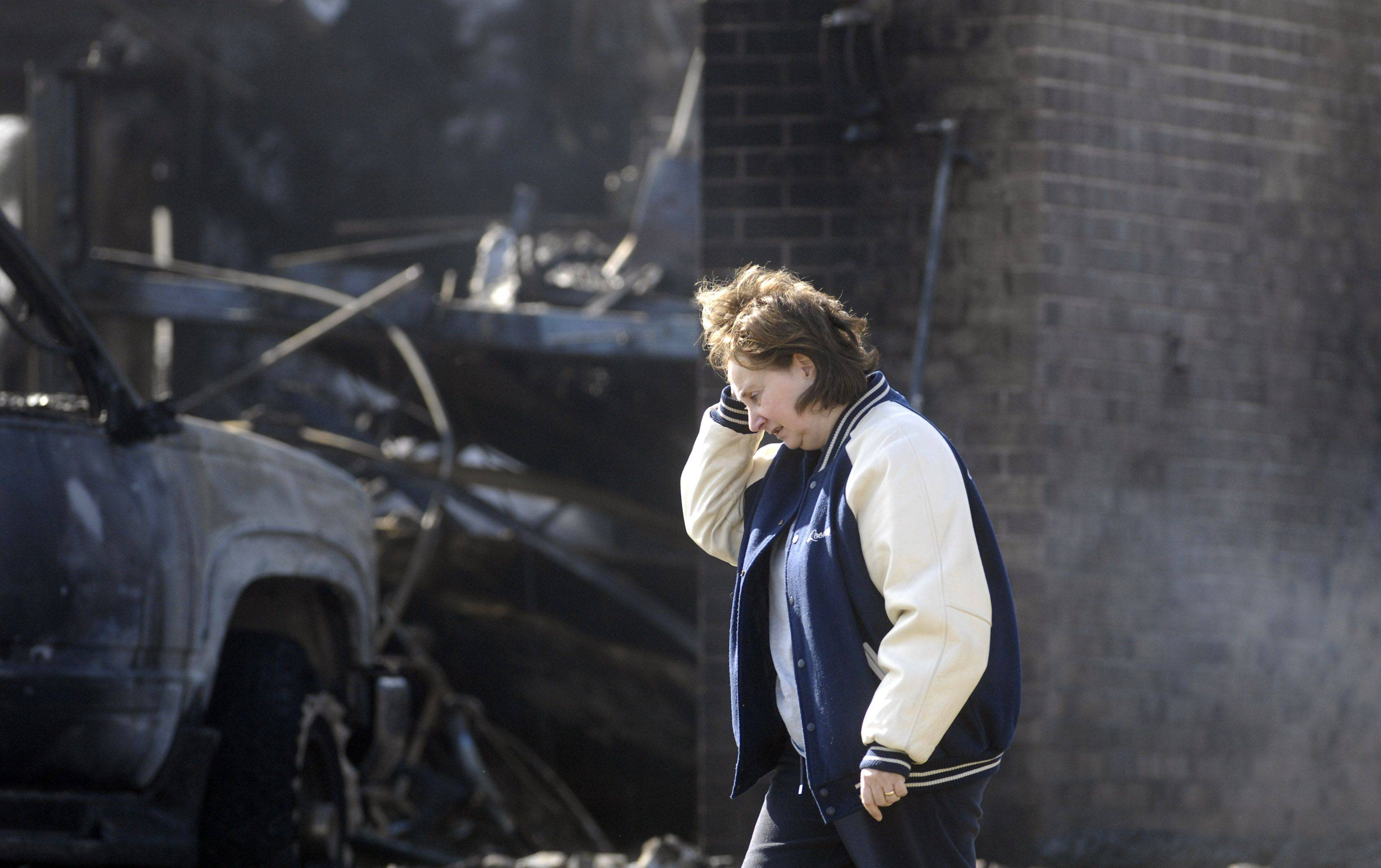 A woman walks past the burned garage and vehicles after a fire at 29W100 Hill Ct. in unincorporated West Chicago.