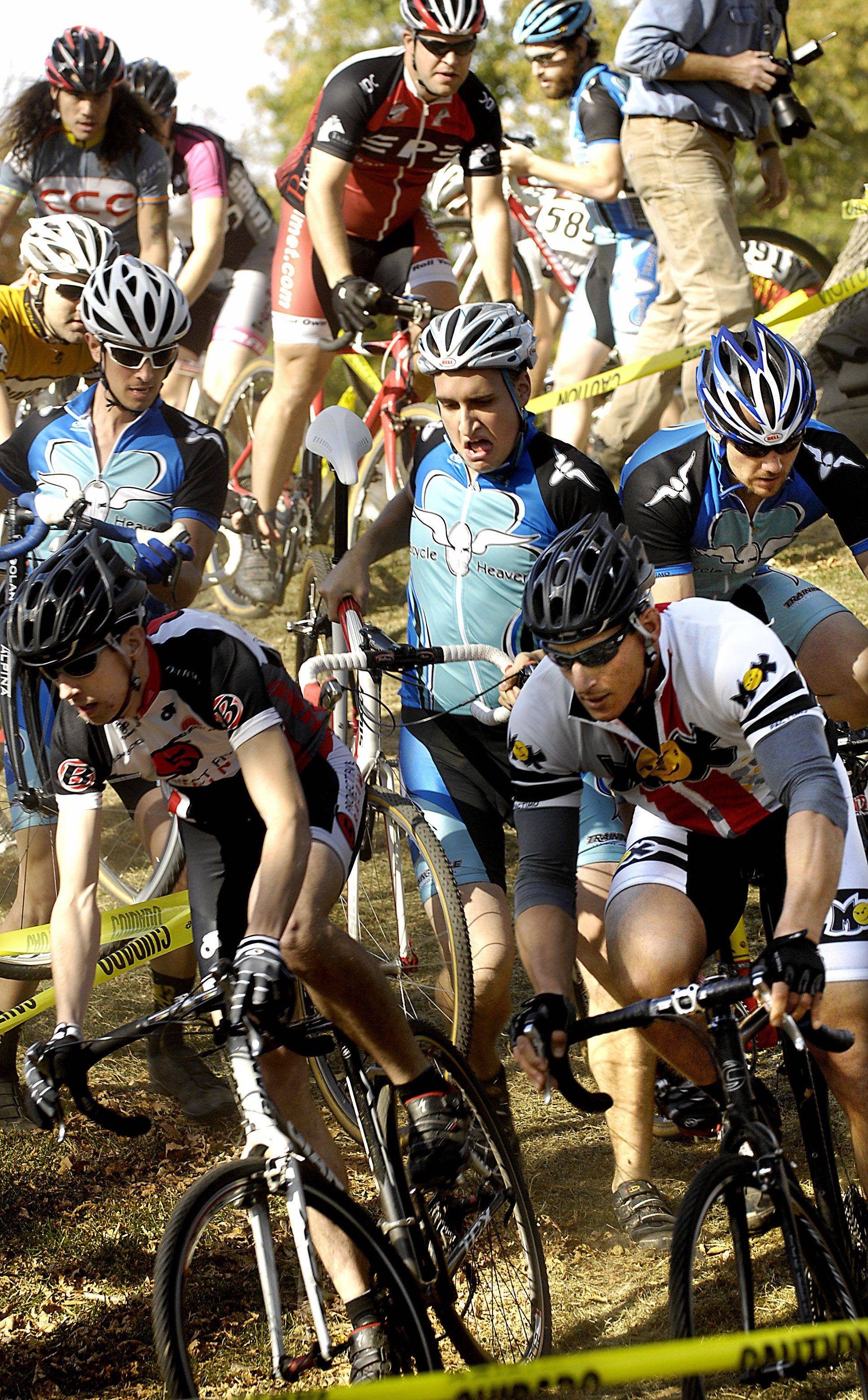Competitors in a cyclocross race in Carpentersville race through a downhill s-curve called Heckle Hill.